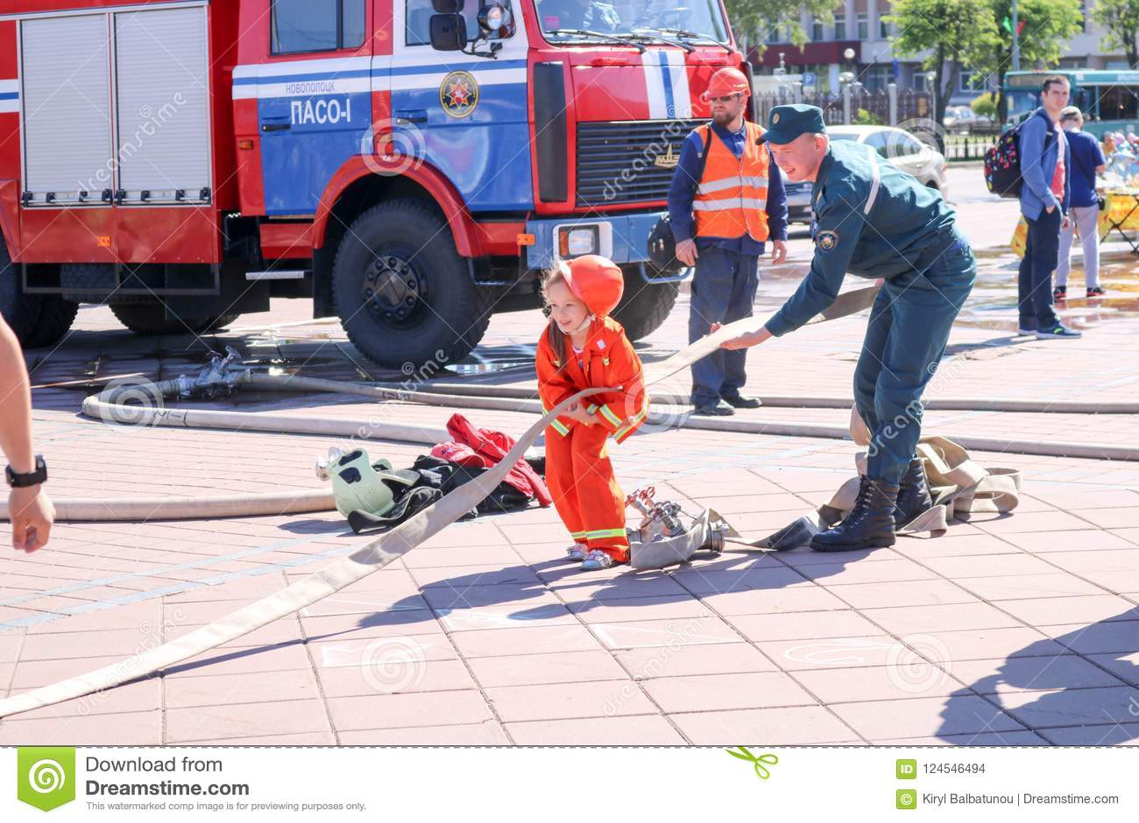 Een brandweerman` s mens onderwijst een klein meisje in een ornery vuurvast kostuum om rond met Wit-Rusland, Minsk, 08 te lopen 0