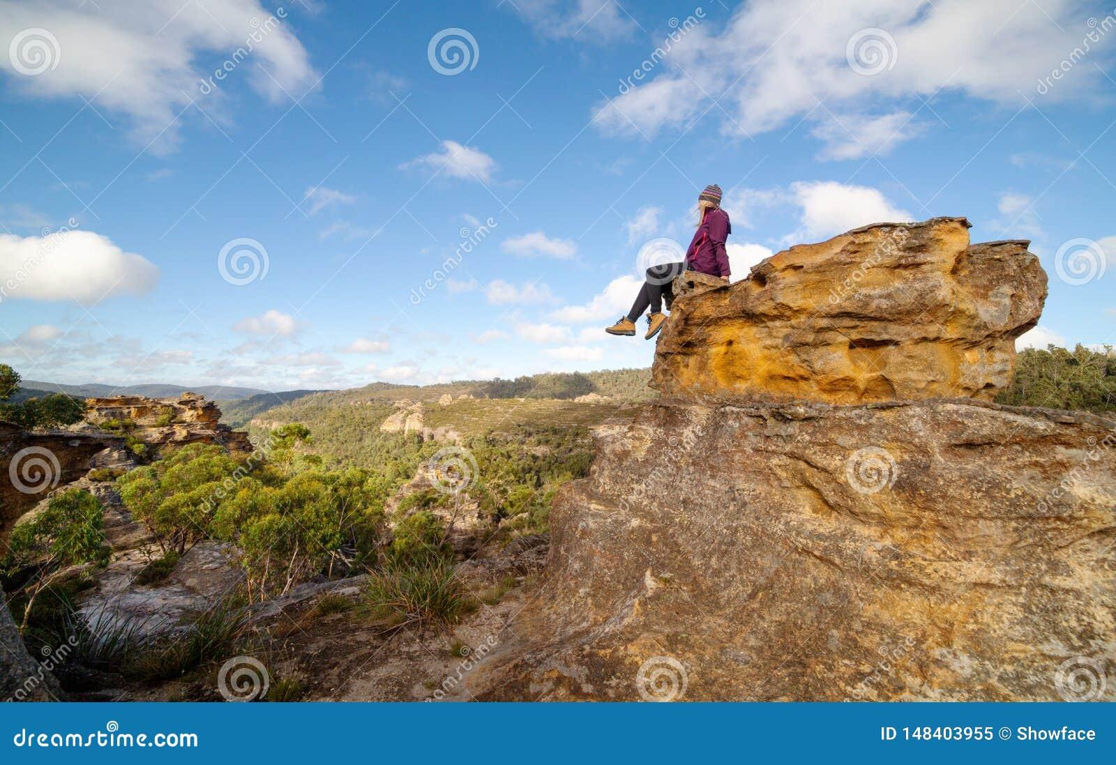 Een bushwalker zit hoog boven op een landschap van pagoden, valleien, geulen en canions