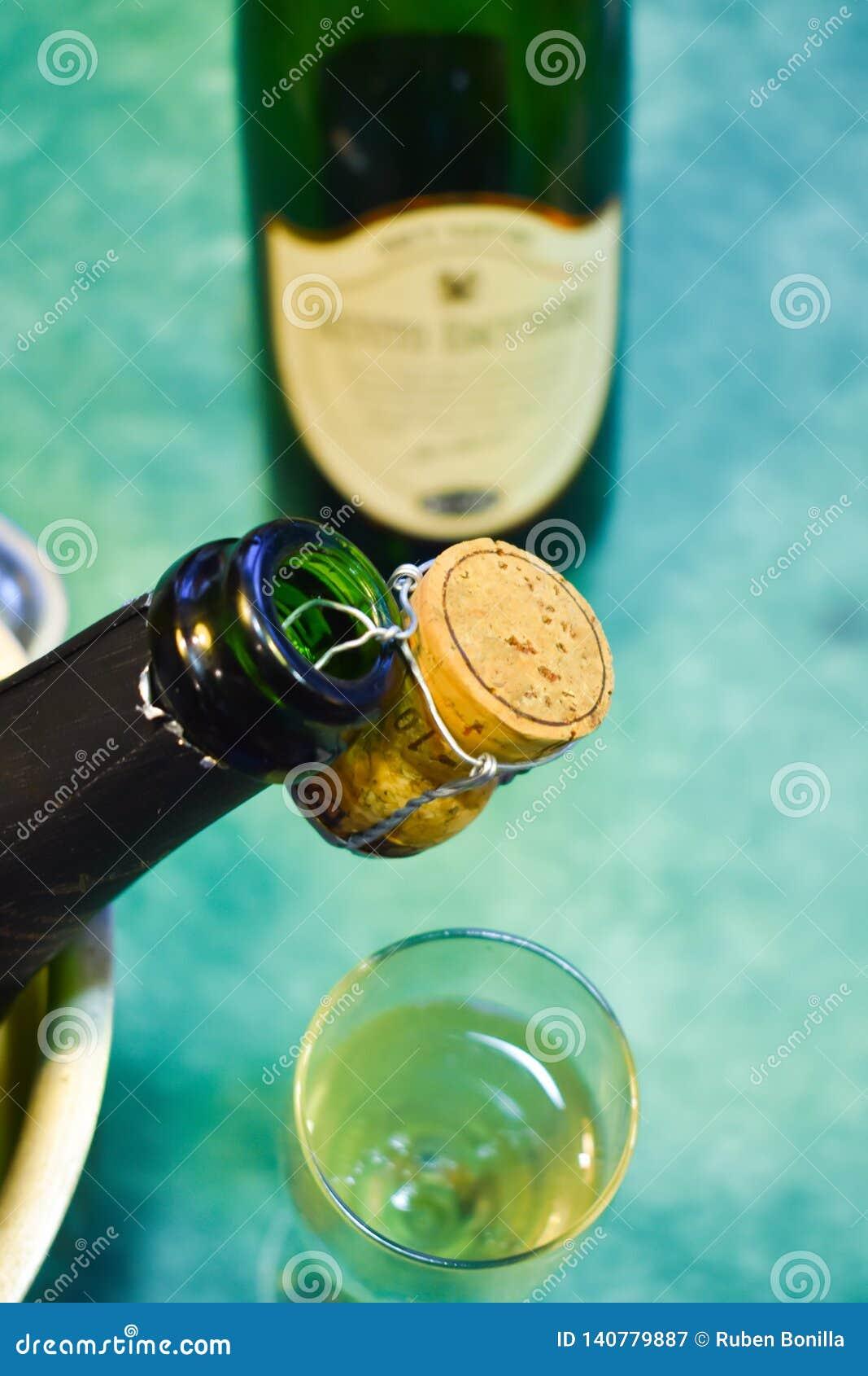 Een champagnefles in een koude emmer met ijs en water, de cork holding van de mond die de scène, een kop met het vonken verfraaie