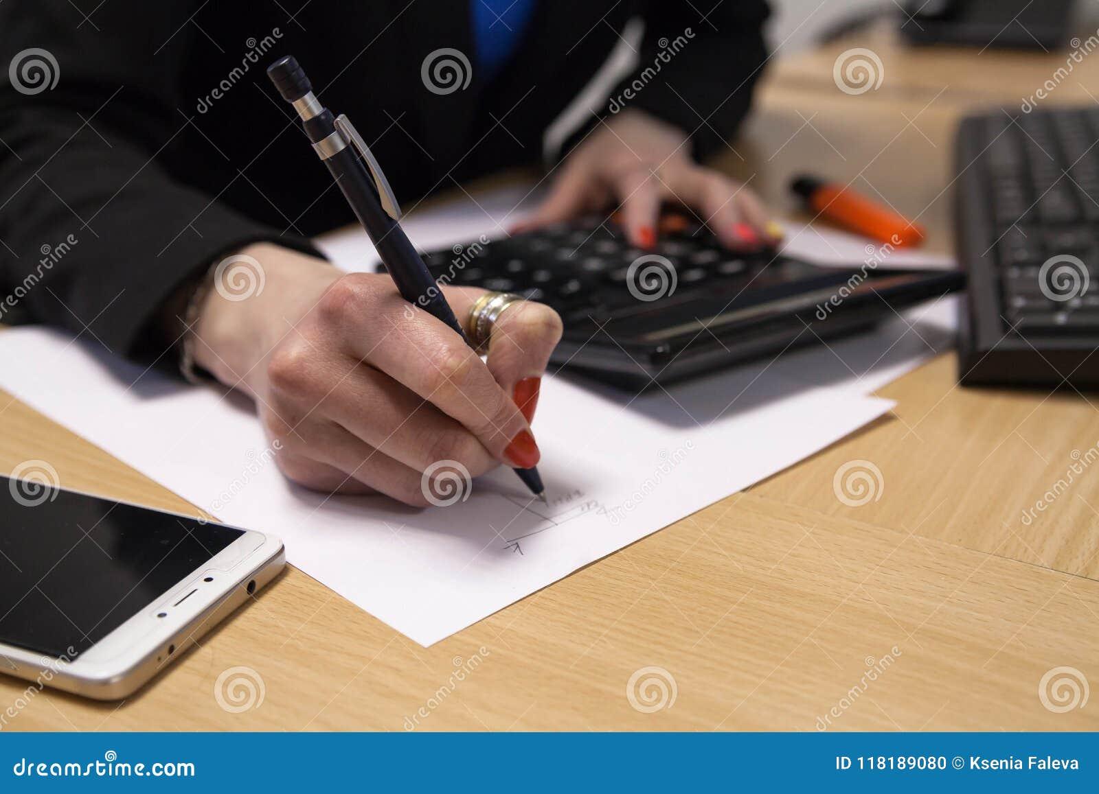 Een close-up, bedrijfsdame, die op een stuk van document schrijven, zit bij haar bureau