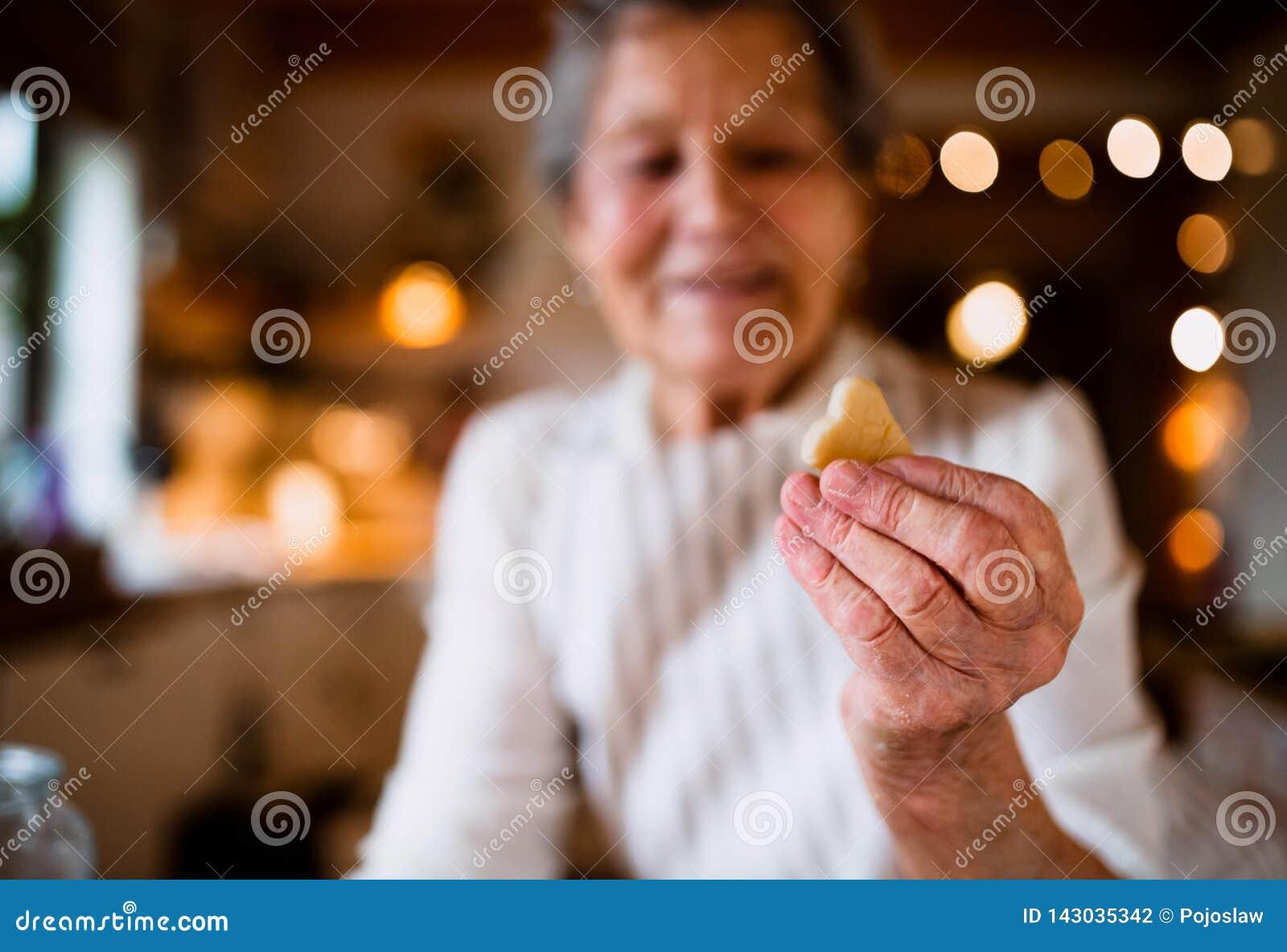 Een close-up die van bejaarde cakes in een keuken maken thuis, een koekje houden