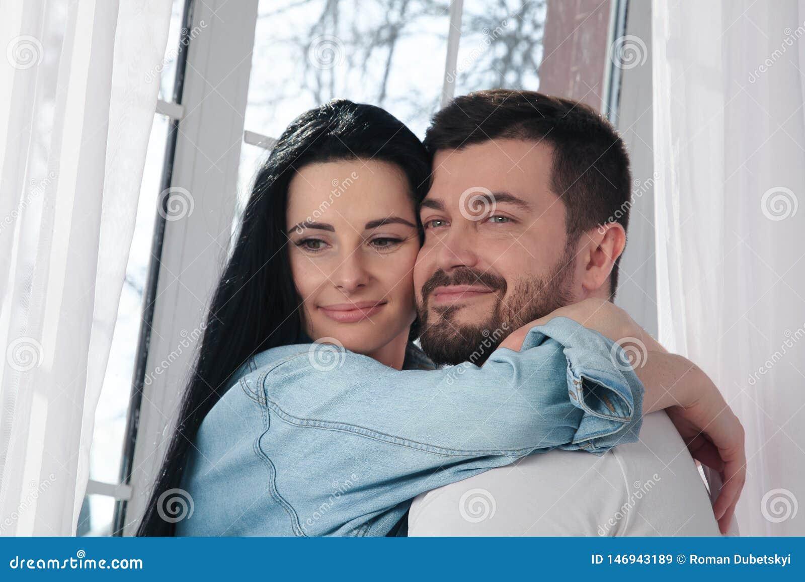 Een close-up van een gelukkig paar die en in de slaapkamer koesteren kussen
