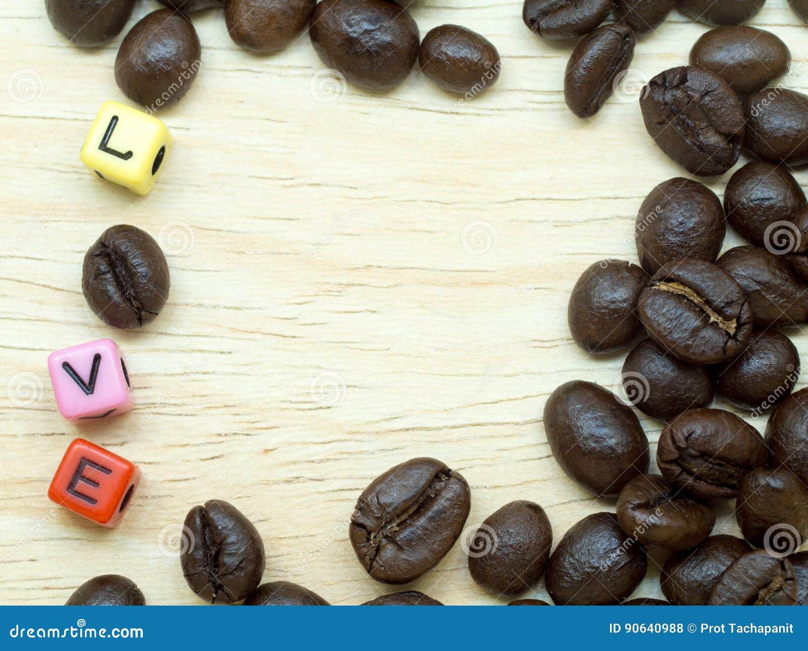 Een cluster van dunne koffiebonen op lichte houten vloer stock