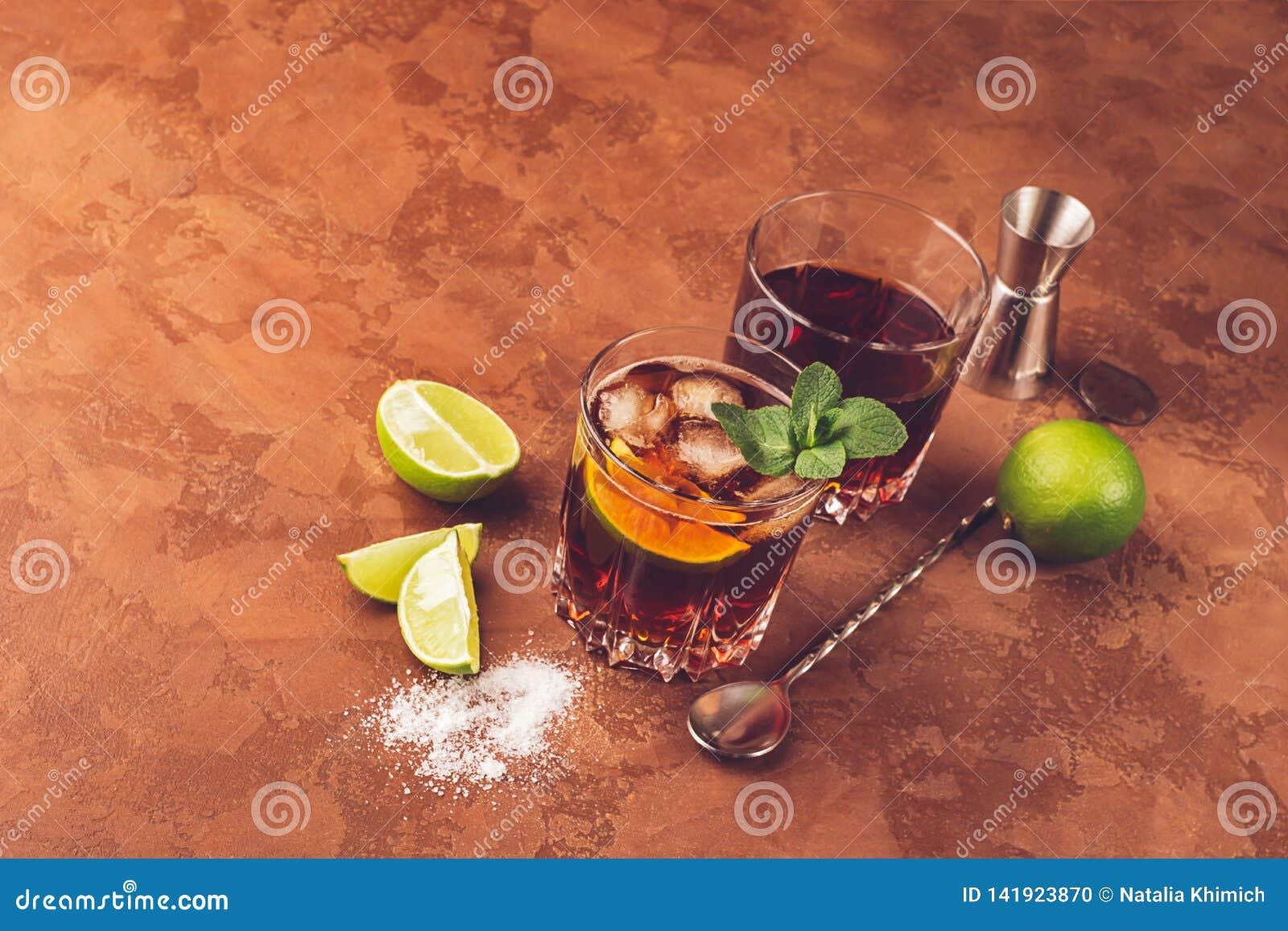 Een cocktail van rumijsblokjes en sappige kalk in glasdrinkbekers tegen een donkere bruine achtergrond Sterke alcoholische drank