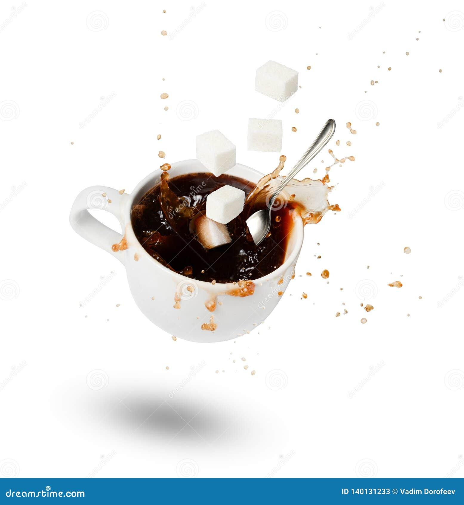 Een dalende kop van koffie, suikerkubussen en een lepel Uitbarstingen en dalingen motie Schaduw Witte geïsoleerde achtergrond