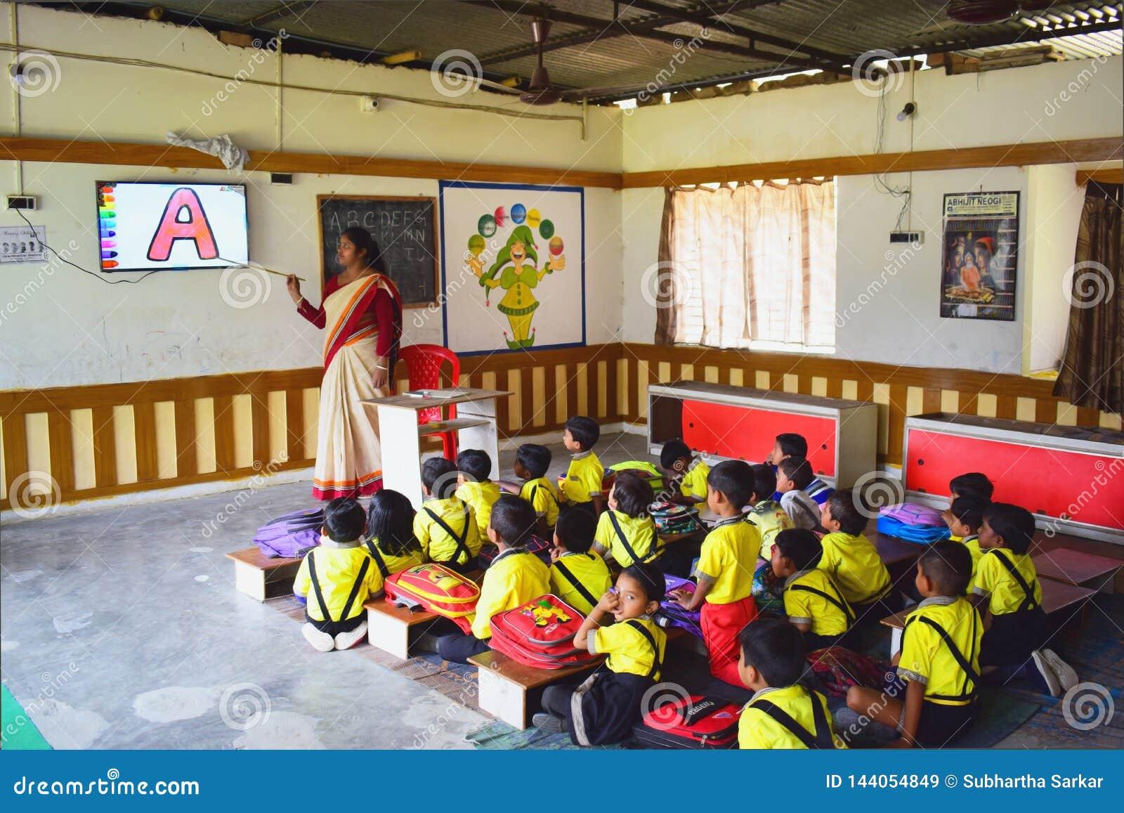 Een dameleraar die audiovisuele klasse van kleuterschoolkinderen nemen in een ruimte