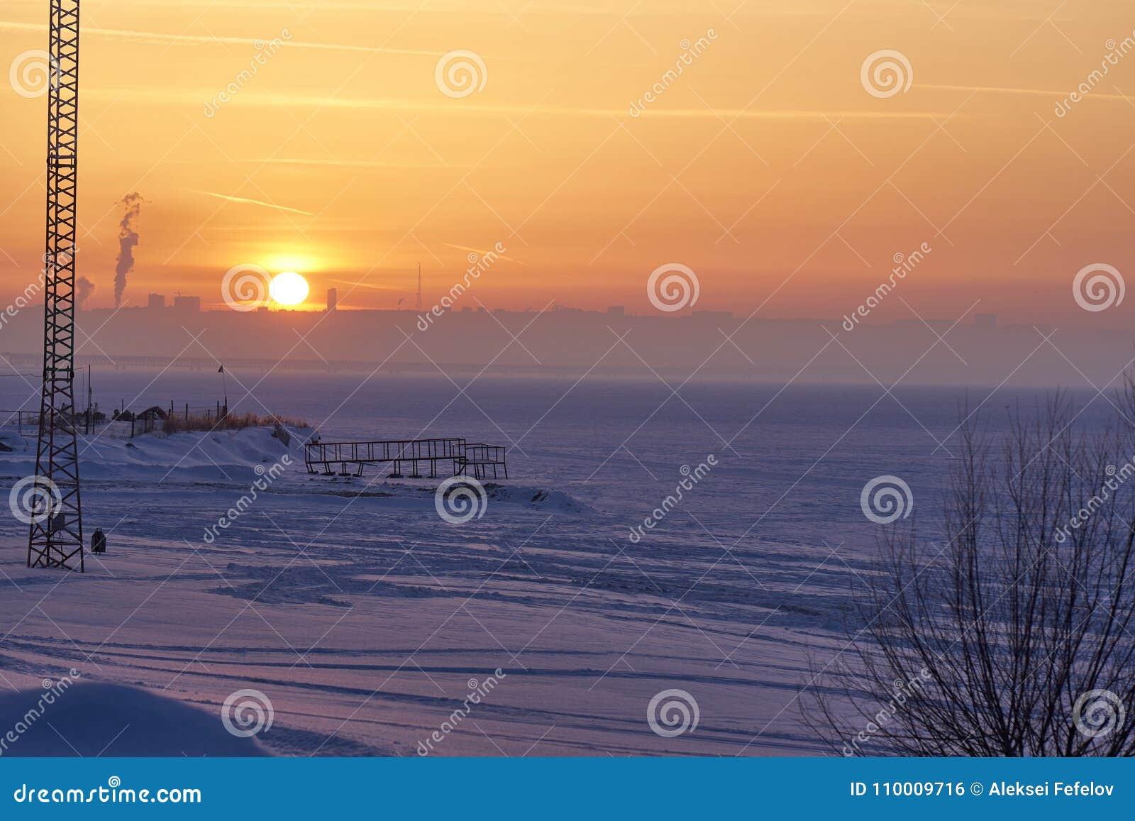 Een de winterzonsondergang over een groot bevroren meer Op de verre bank in de nevel zijn zichtbare silhouetten van gebouwen De s