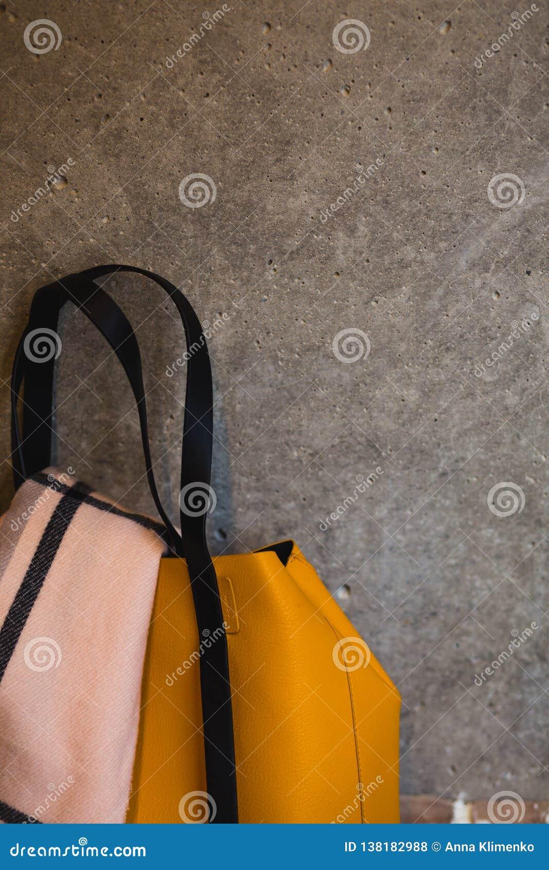 Een deel van gele leer vrouwelijke zak op grijze muur backgroud