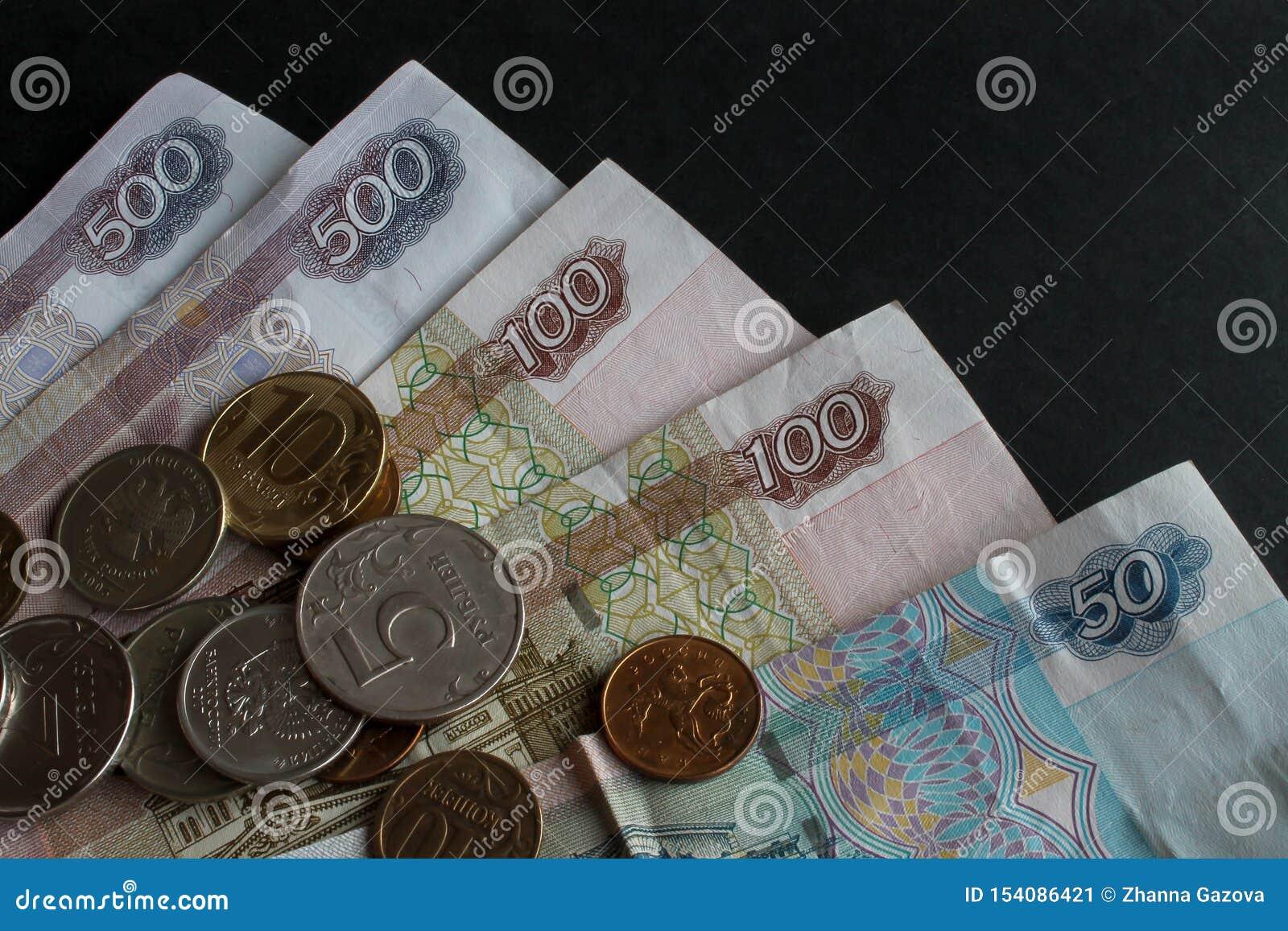 Een deel van Russisch papiergeld en het verspreiden zich van metaalmuntstukken van verschillende benamingen op hen close-up op ee