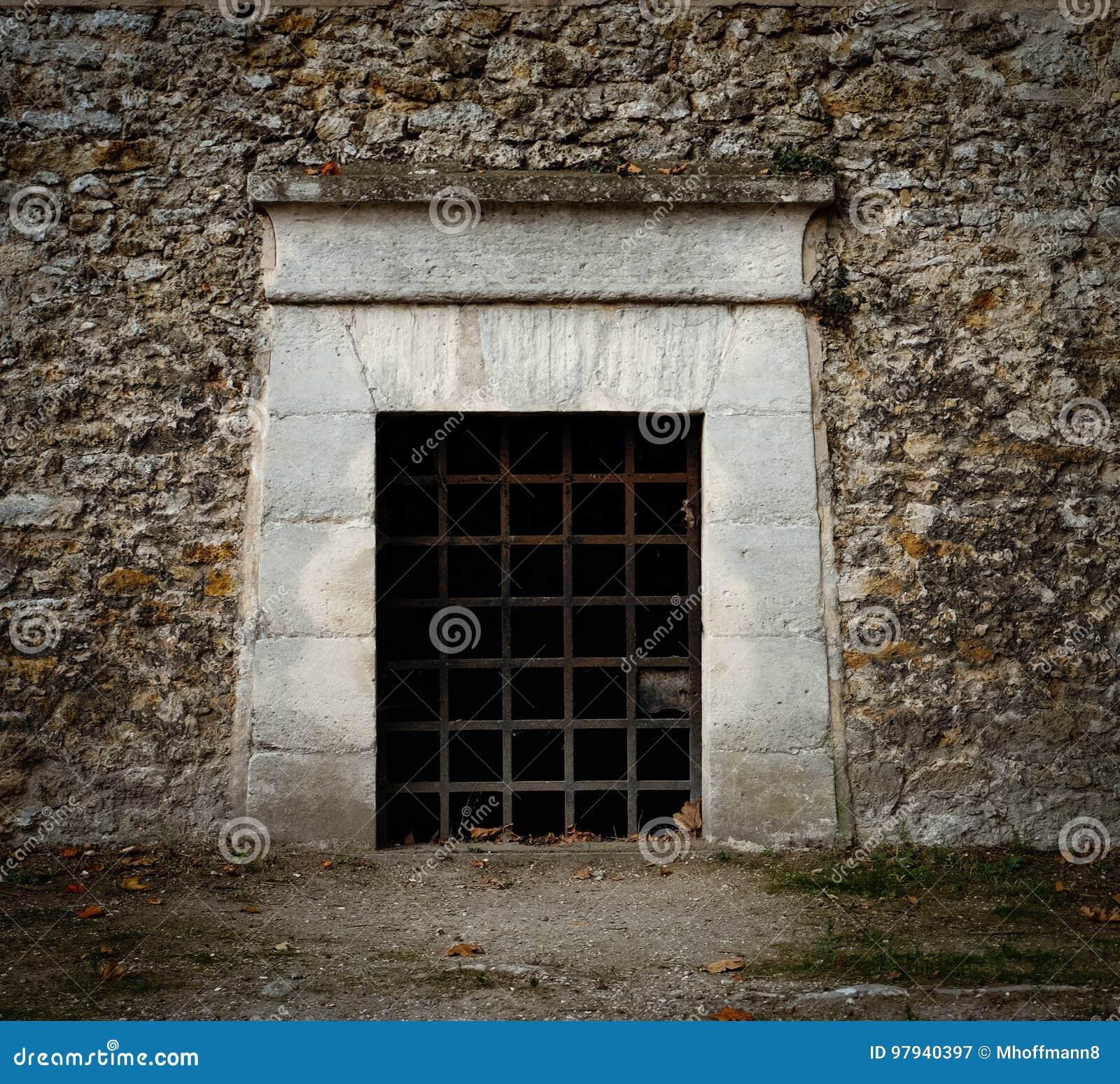 Een deur met roestig ijzer verspert - als een ingang aan een kerker, een graf of een oude gevangenis