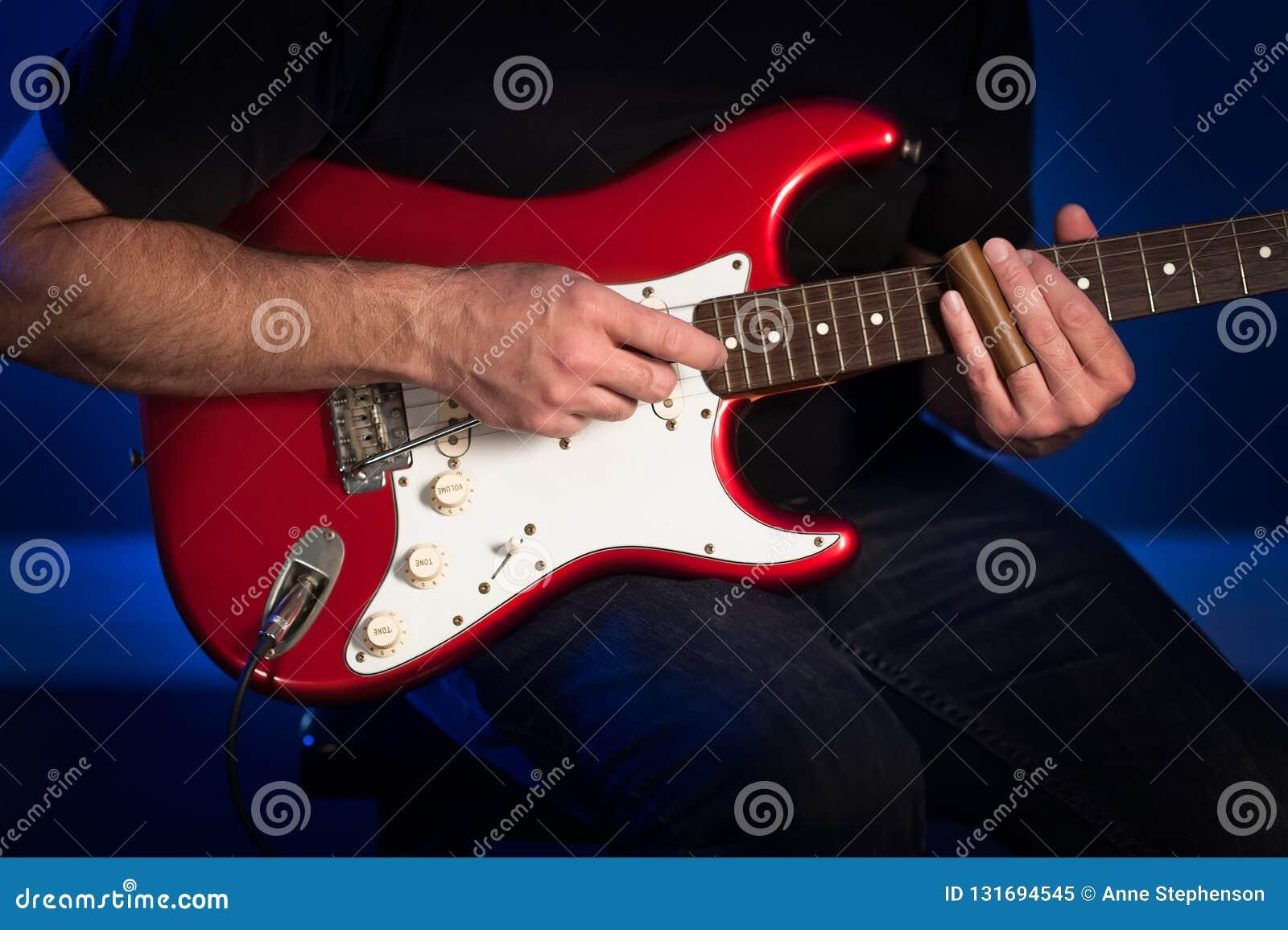 Een dichte omhooggaande mening van een mens die een rode en witte elektrische gitaar spelen