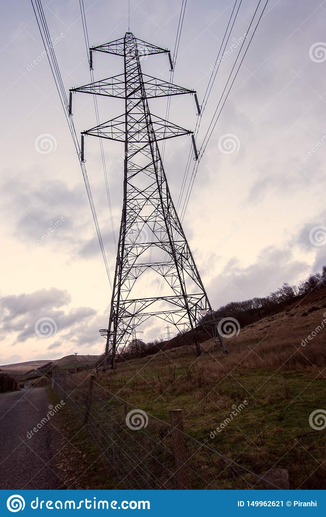 Een donkere grote transmissietoren, elektriciteitspyloon, bevindt zich tegen een gele zonsondergang