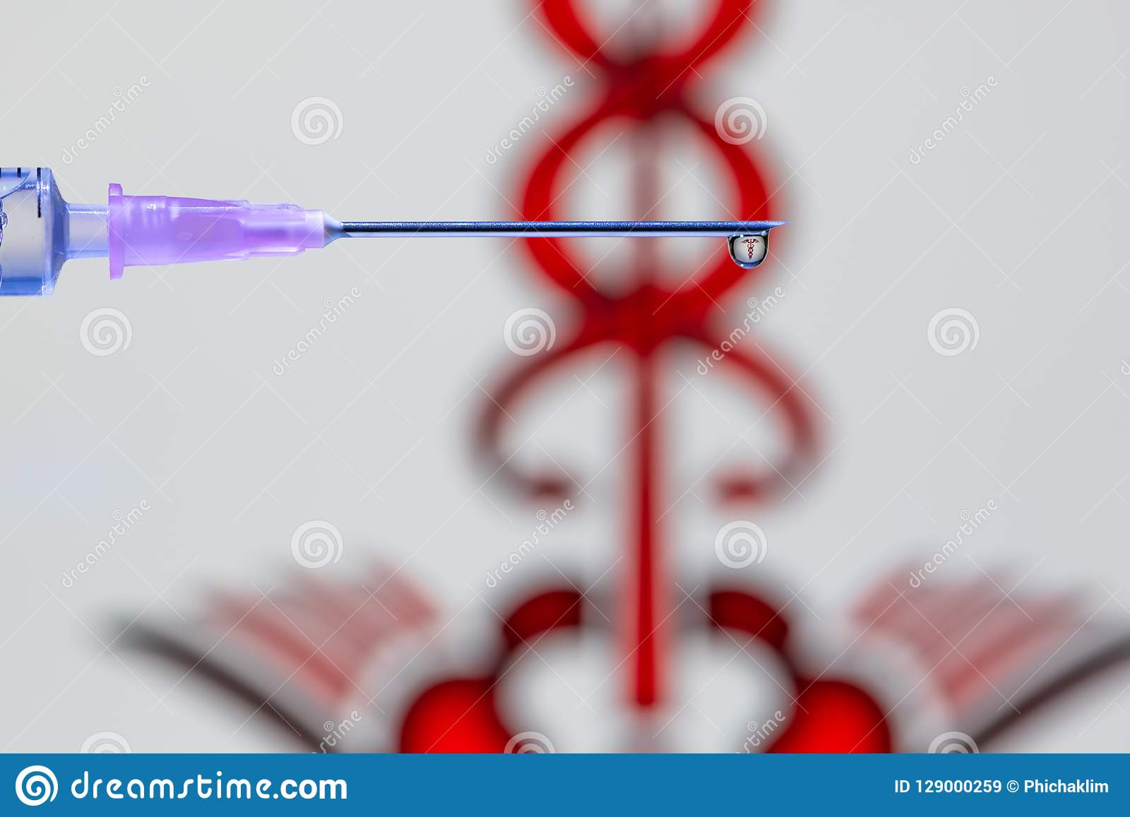 Een druppeltje van vaccin bij het uiteinde van de naald en de spuit