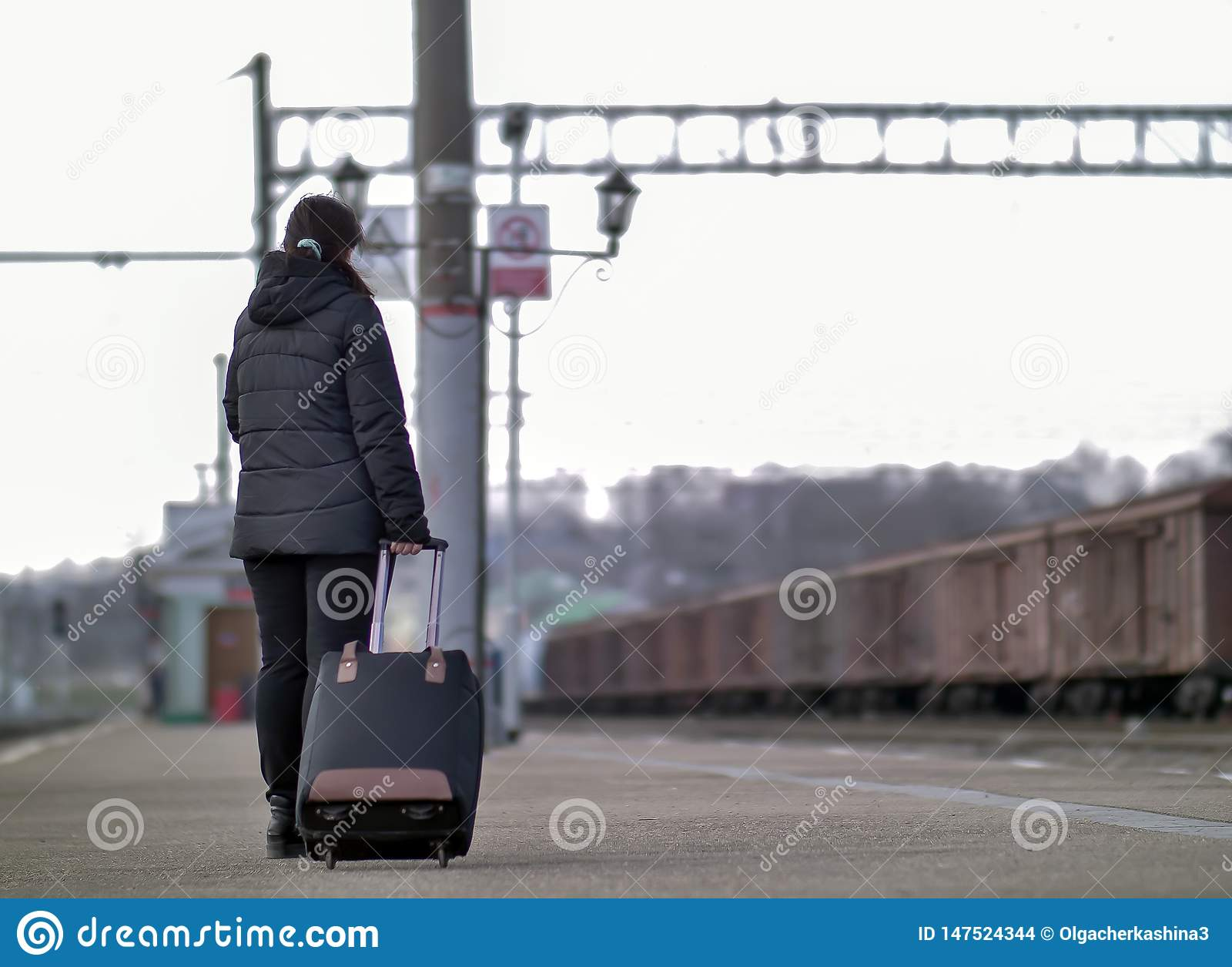 Een eenzaam meisje met een zwarte koffer bevindt zich op het platform wachtend op de trein