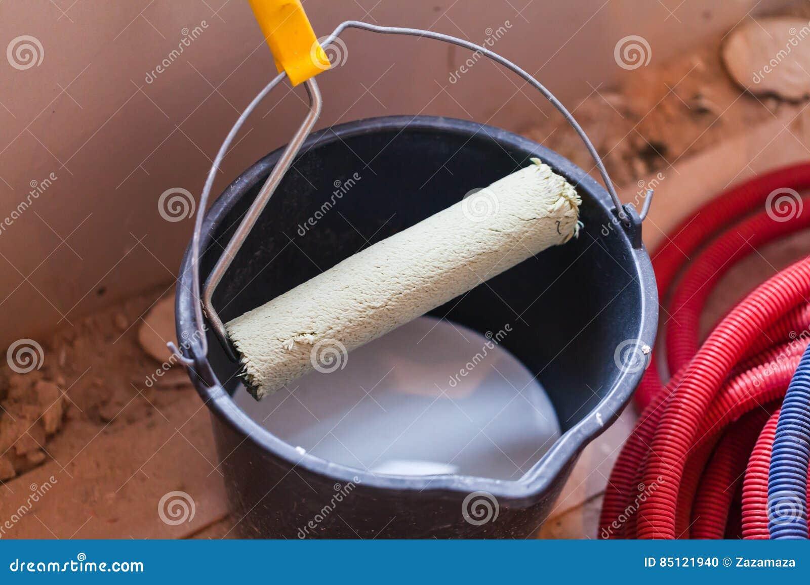 Een emmer met witte verf en een rol op een flat is in aanbouw