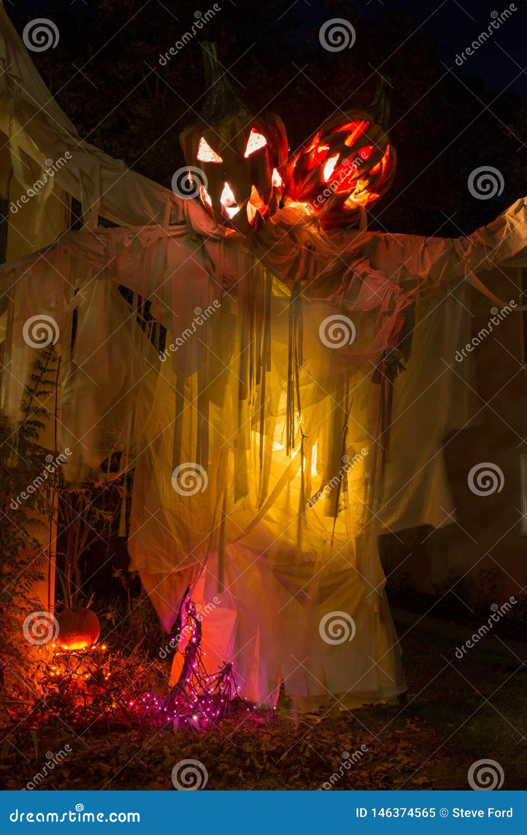 Een enge vertoning van twee leidde pompoenspook bij nacht met gele verlichting die aan dit Halloween kijkend vertoning toevoegt