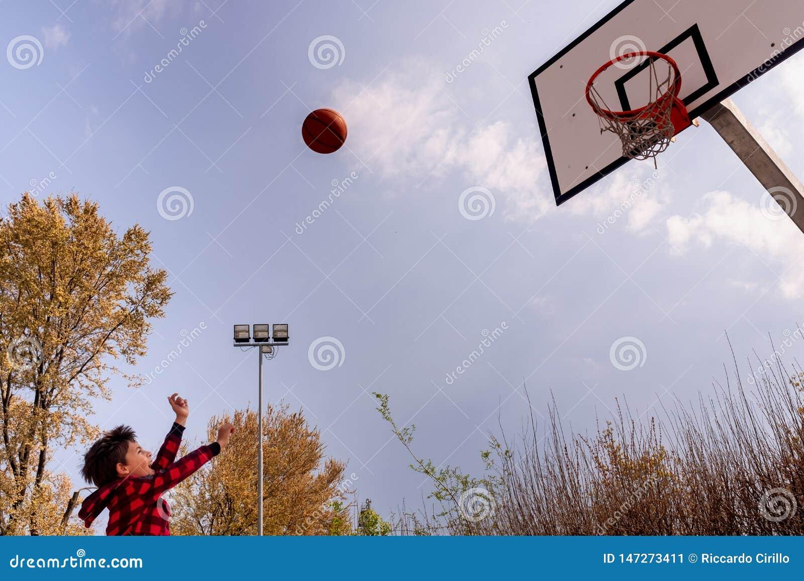 Een enthousiast kind maakt een basketbalschot