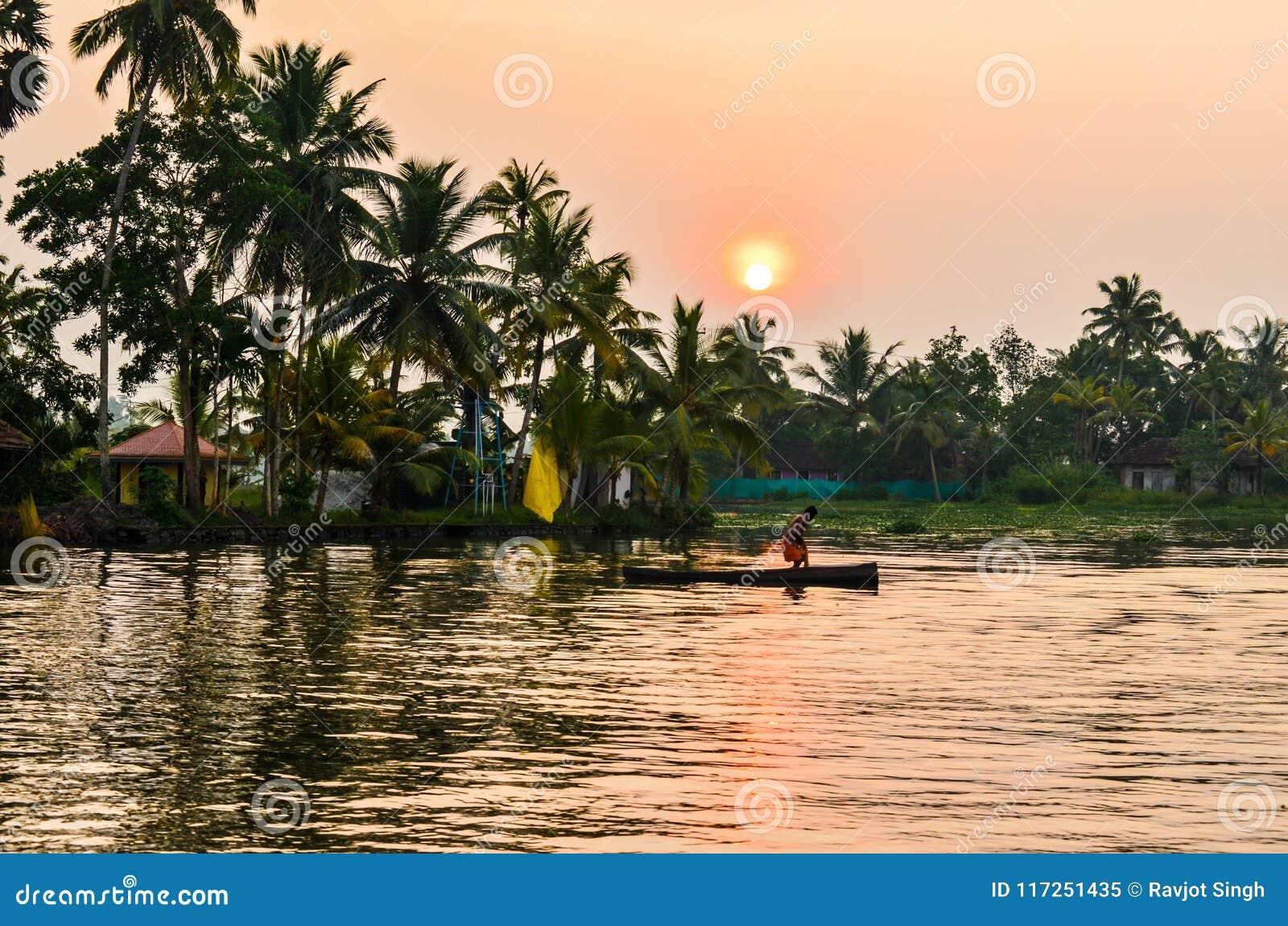 Een fascinatiemening van een boot met boatman, bomen, huizen, landschap op binnenwateren in Kerala, Zuid-India