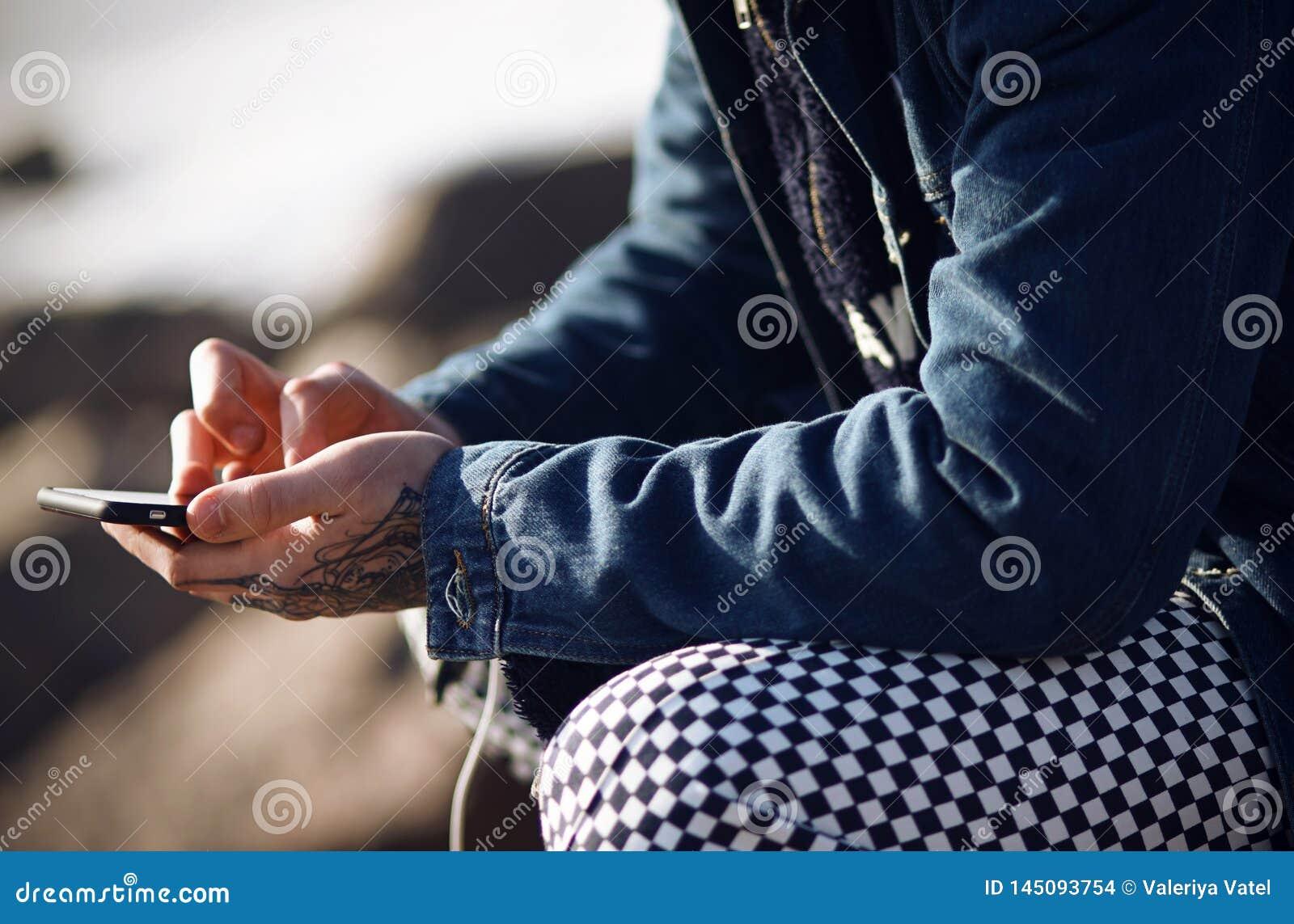 Een fashionably geklede mens houdt een aanrakingstelefoon