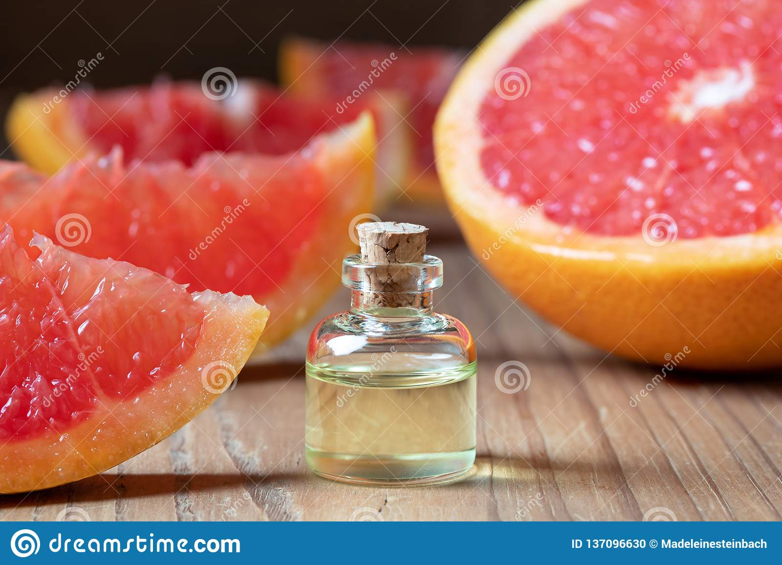 Een fles grapefruitetherische olie met verse roze grapefruit op een lijst