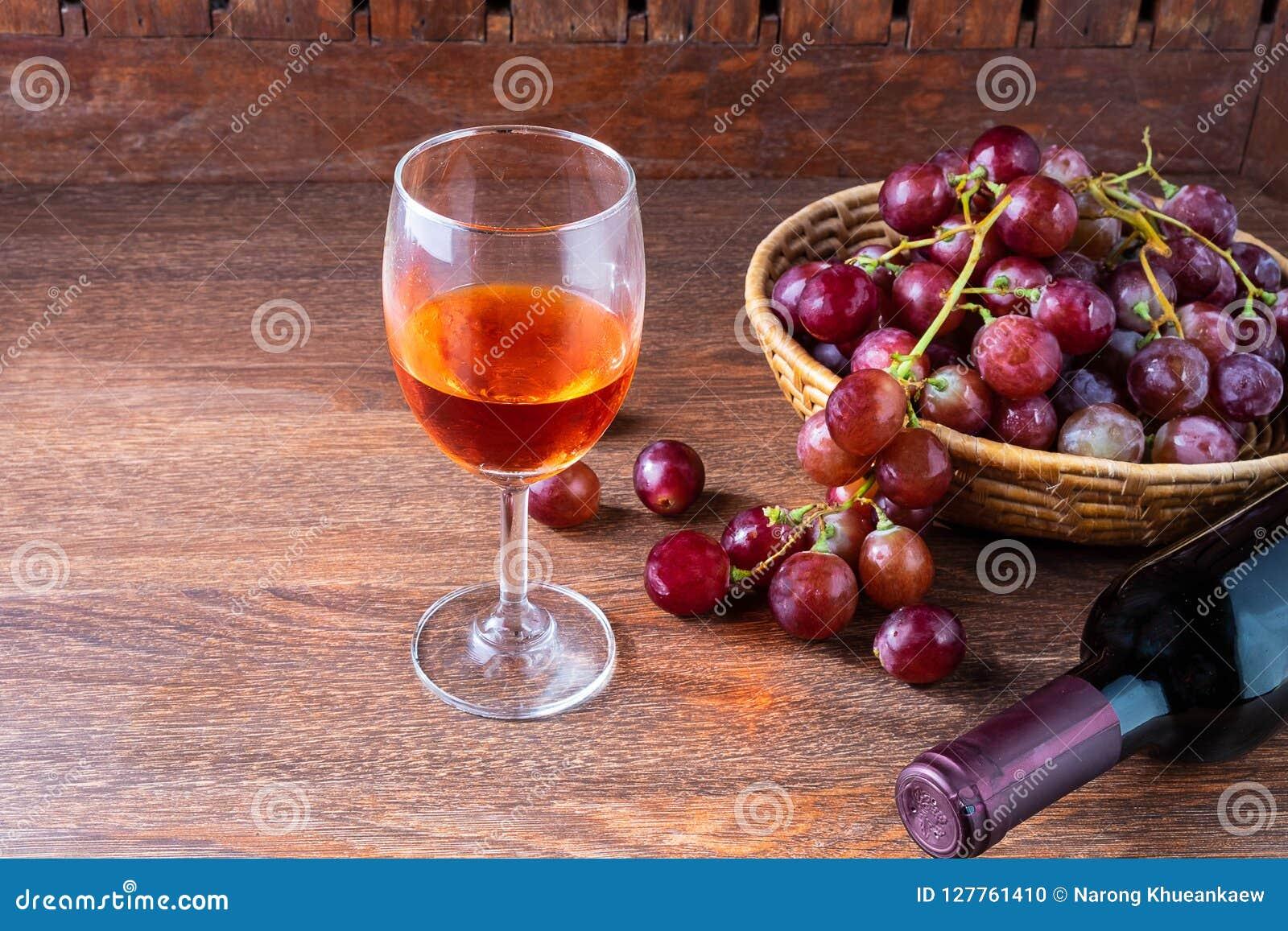 Een fles rode wijn en een glas rode wijn met rode binnen druiven