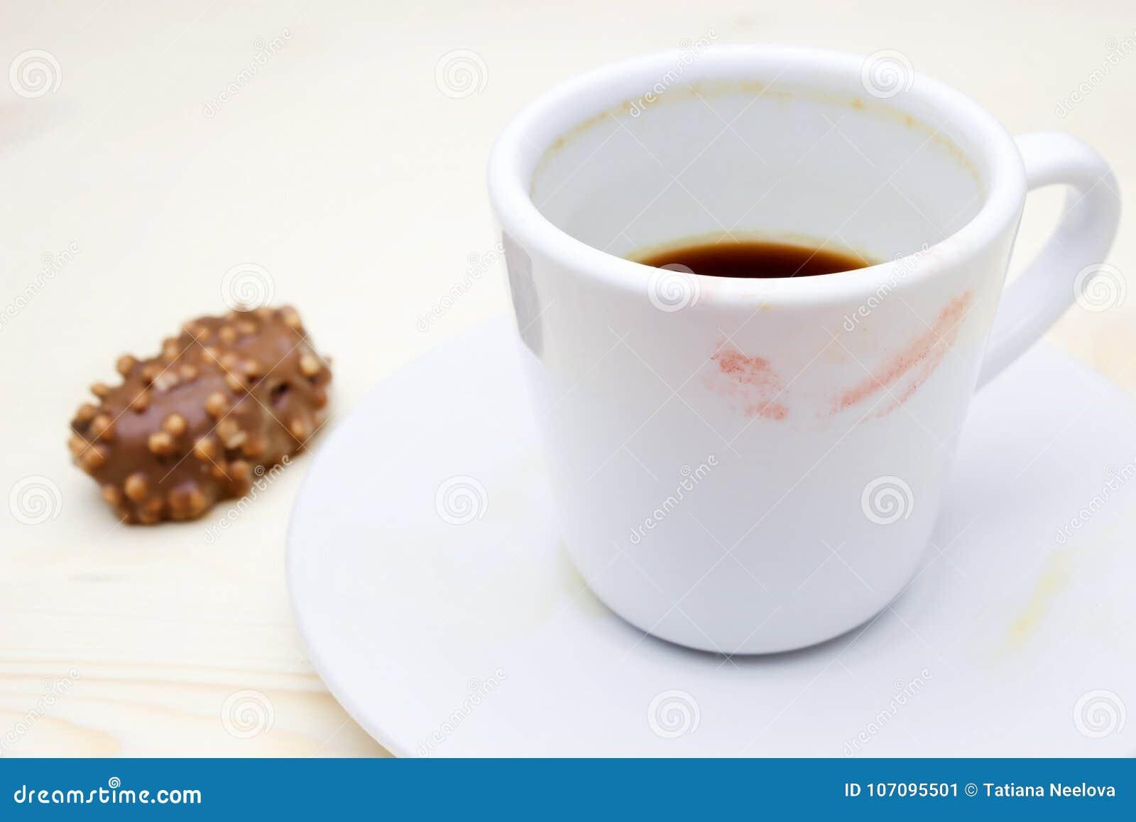 Een foto van de rode lippenstifttekens op uw koffiekop Vuile lege witte porseleinkop op de plaat en een chocoladesuikergoed Messt
