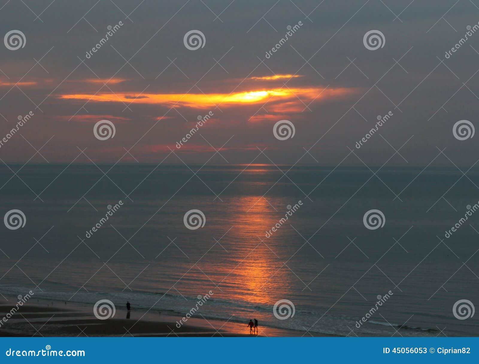 Een gang in het zonsonderganglicht op de kust van het overzees