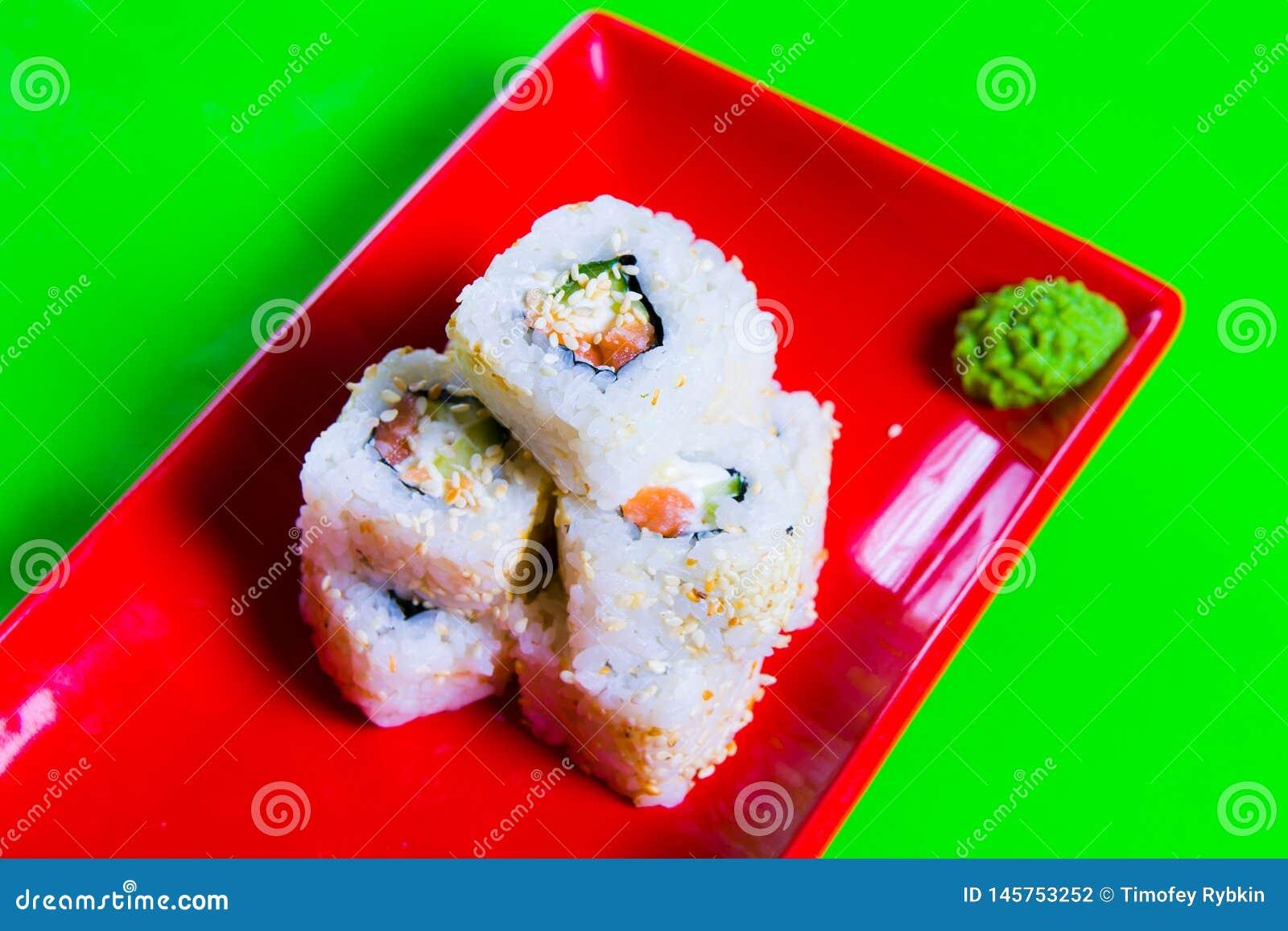Een gedeelte sushi op een rode plaat Groene Achtergrond