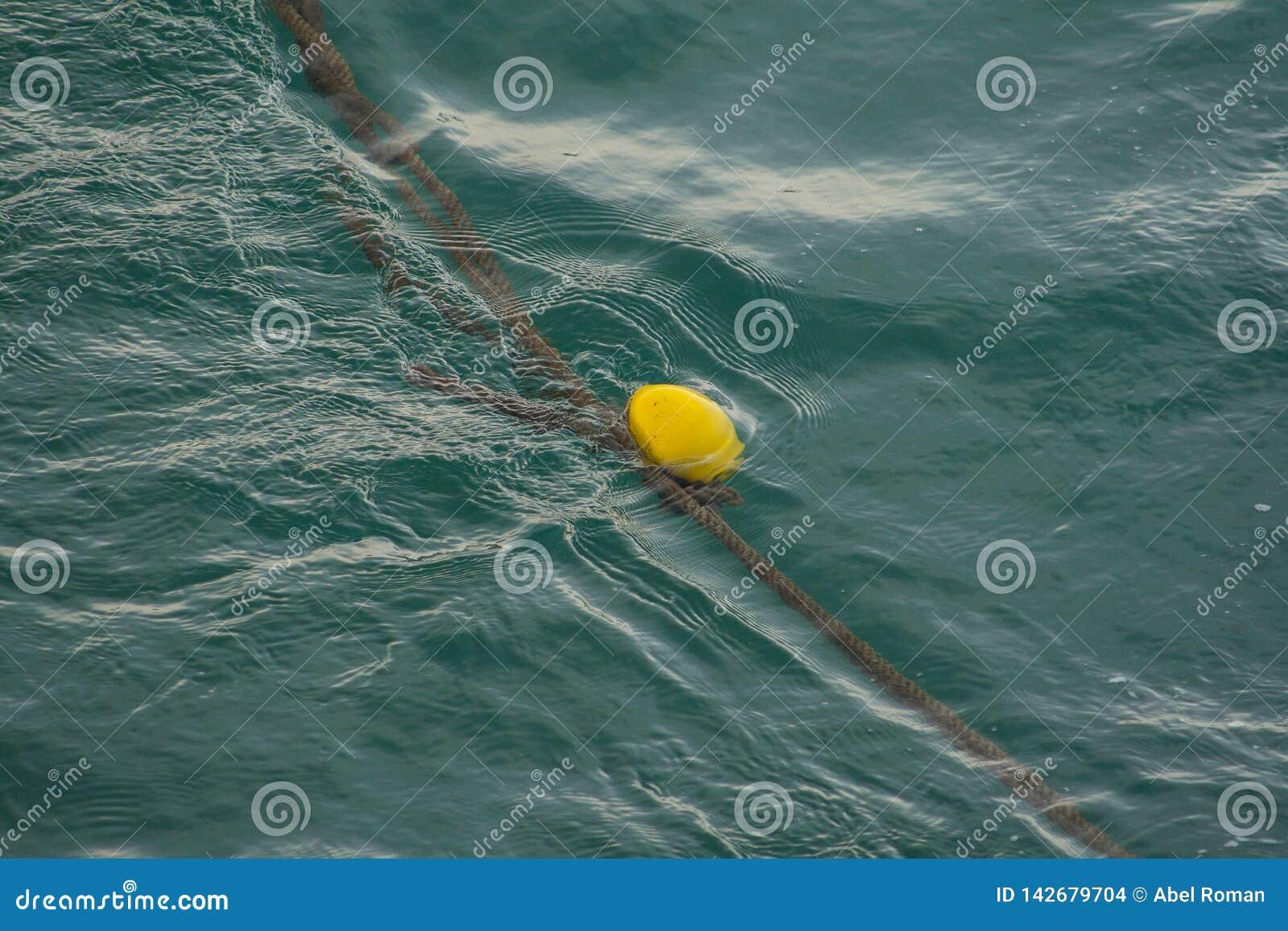 Een gele boei die in het overzees drijven