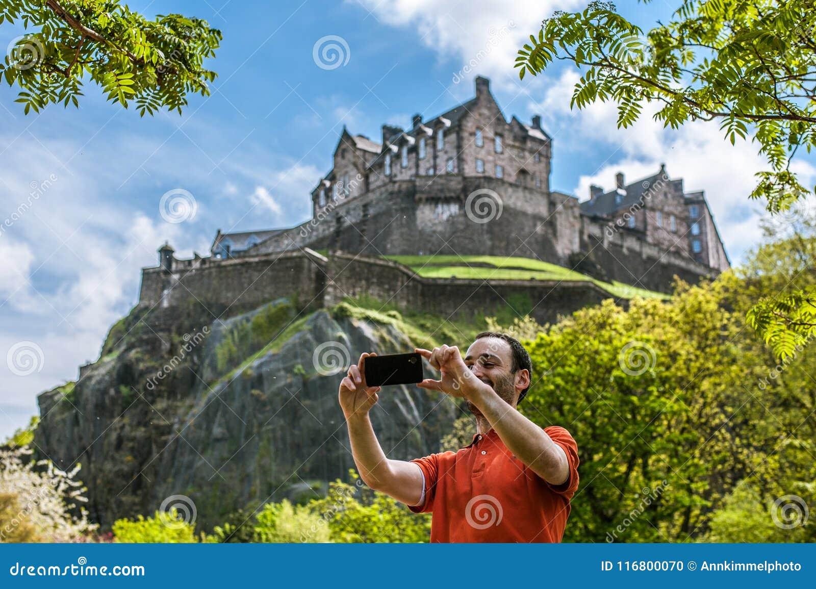 Een gelukkige jonge mensentoerist bij het Kasteel die van Edinburgh selfie op m nemen