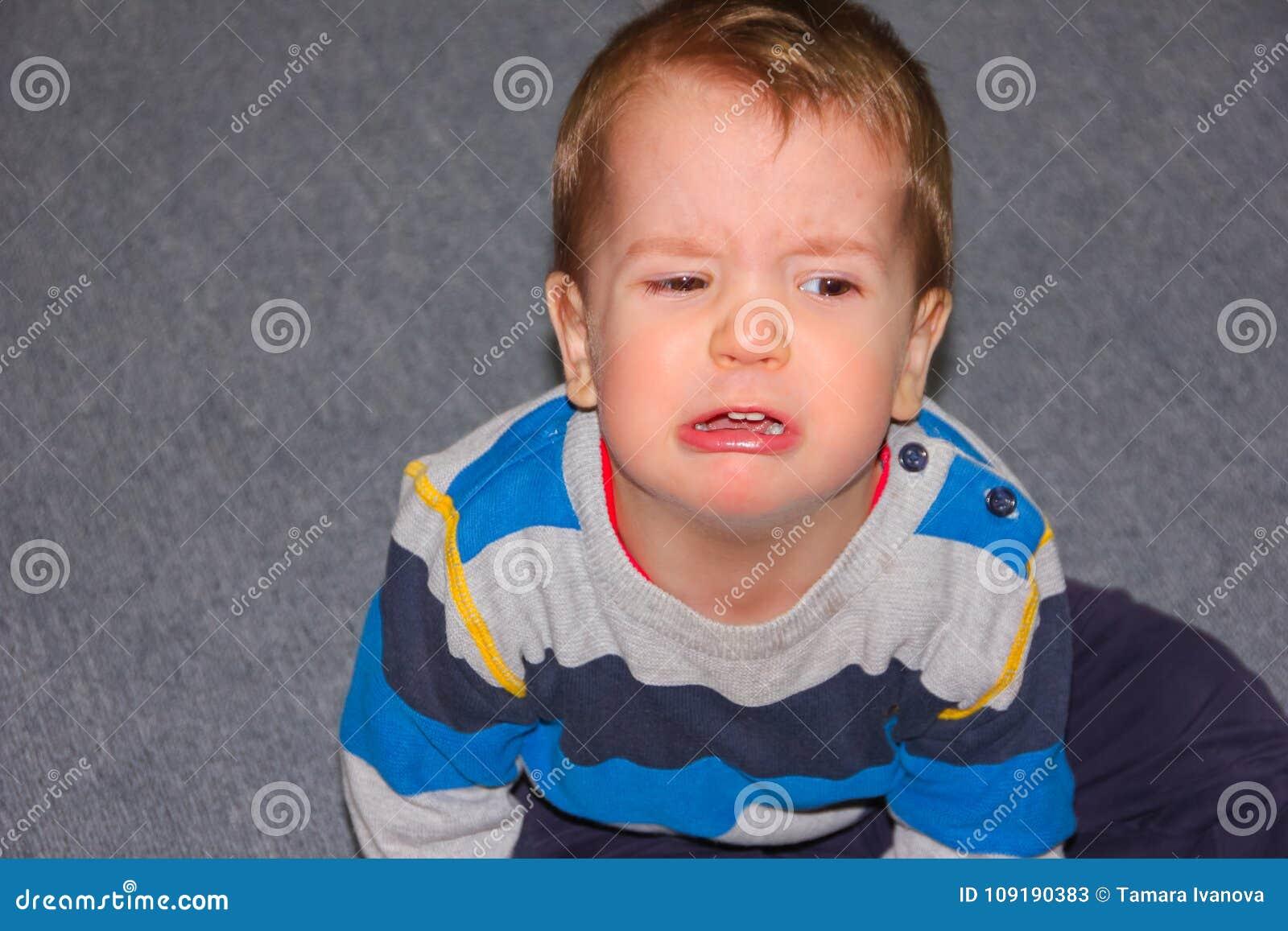 Een geraspt en gekwetst kind zit op de vloer De kleine gepruilde jongen