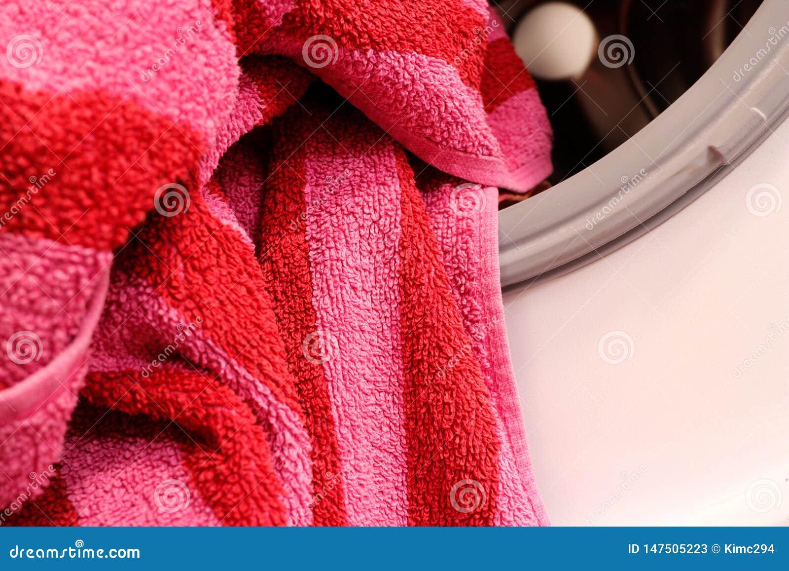 Een gestreepte badhanddoek ligt op de rand van een wasmachinetrommel