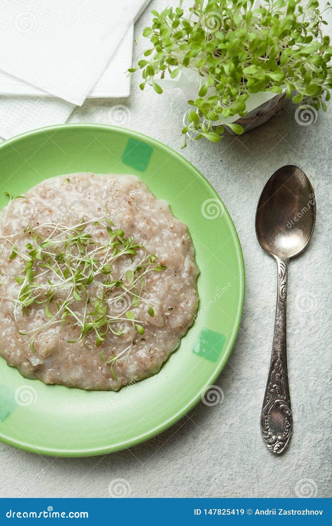 Een gezond ontbijt voor een gezonde levensstijl Multi-graangewassengraangewas met vitaminen op een plaat, een lepel dichtbij Groe