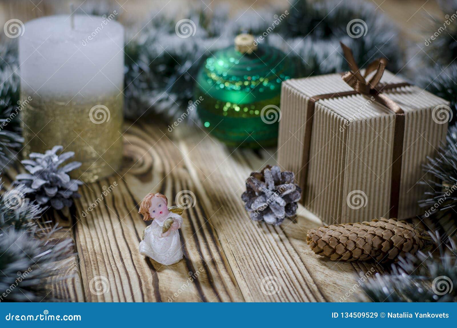 Een gift legt op een houten lijst naast een kaars, kegels en een engel tegen de achtergrond van Kerstmisdecoratie