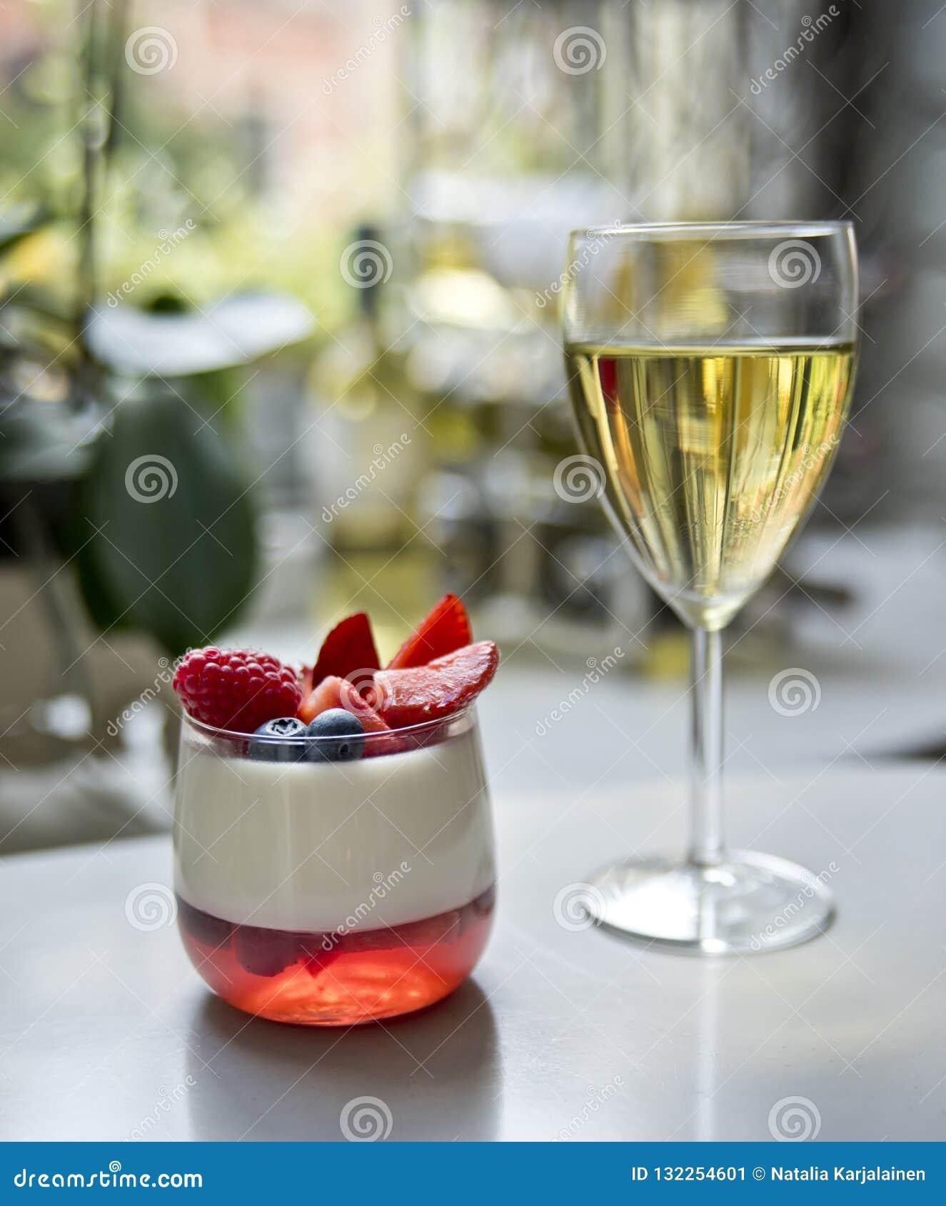 Een glas van witte wijn en een panakotadessert