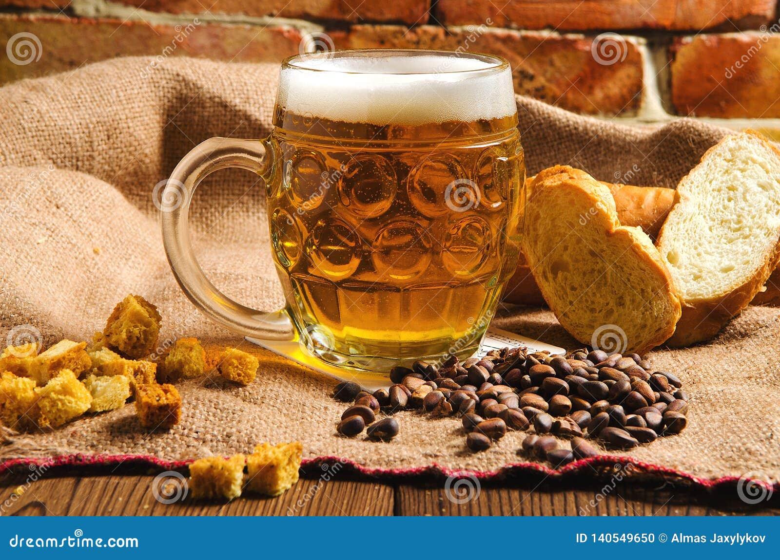 Een glas vers koud licht bier met brood op jute