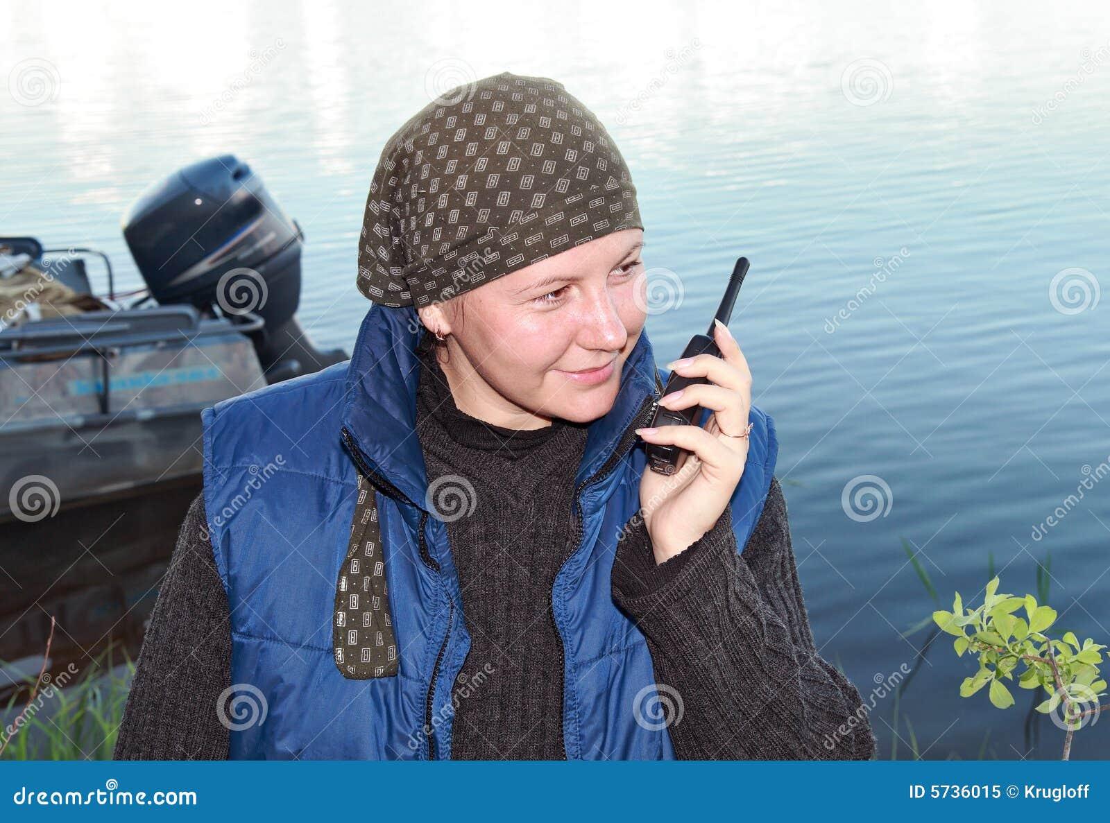 Een glimlachend meisje spreekt op een draagbare radioreeks