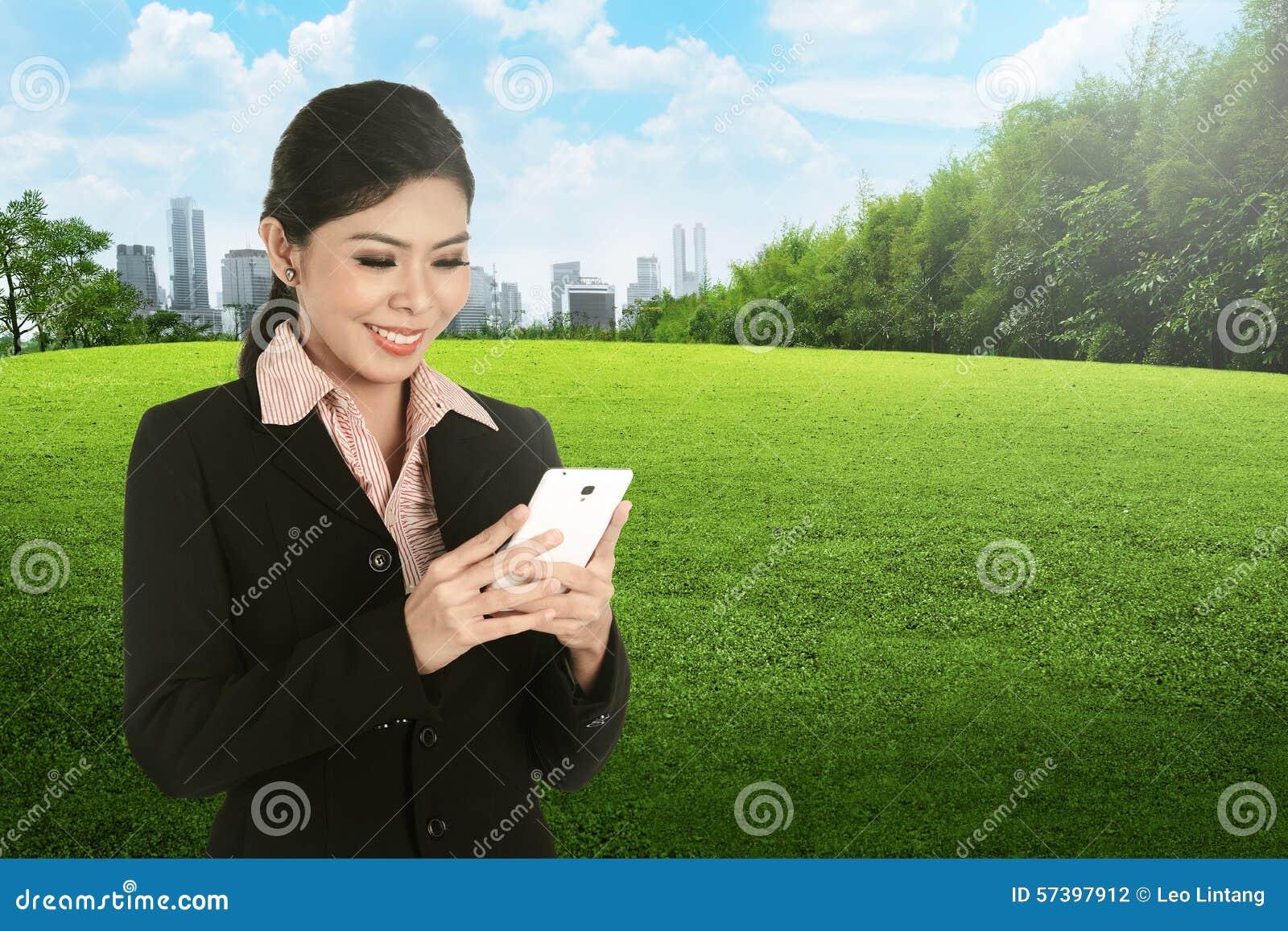 Een Glimlachende Aziatische bedrijfsvrouw die cellphone gebruiken