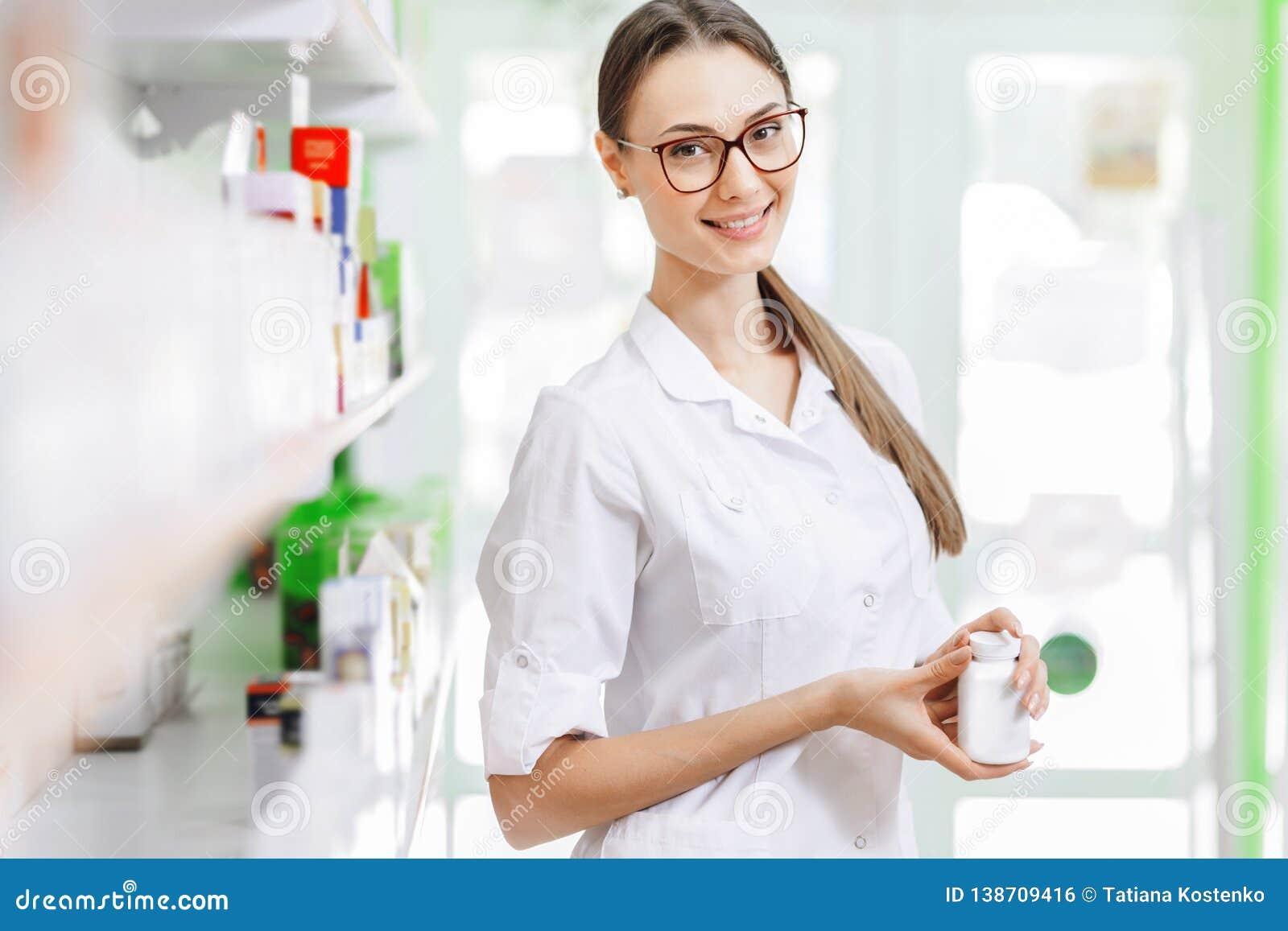 Een glimlachende charmante slanke donker-haired dame met glazen, die een witte laag dragen, bevindt zich naast de plank en toont