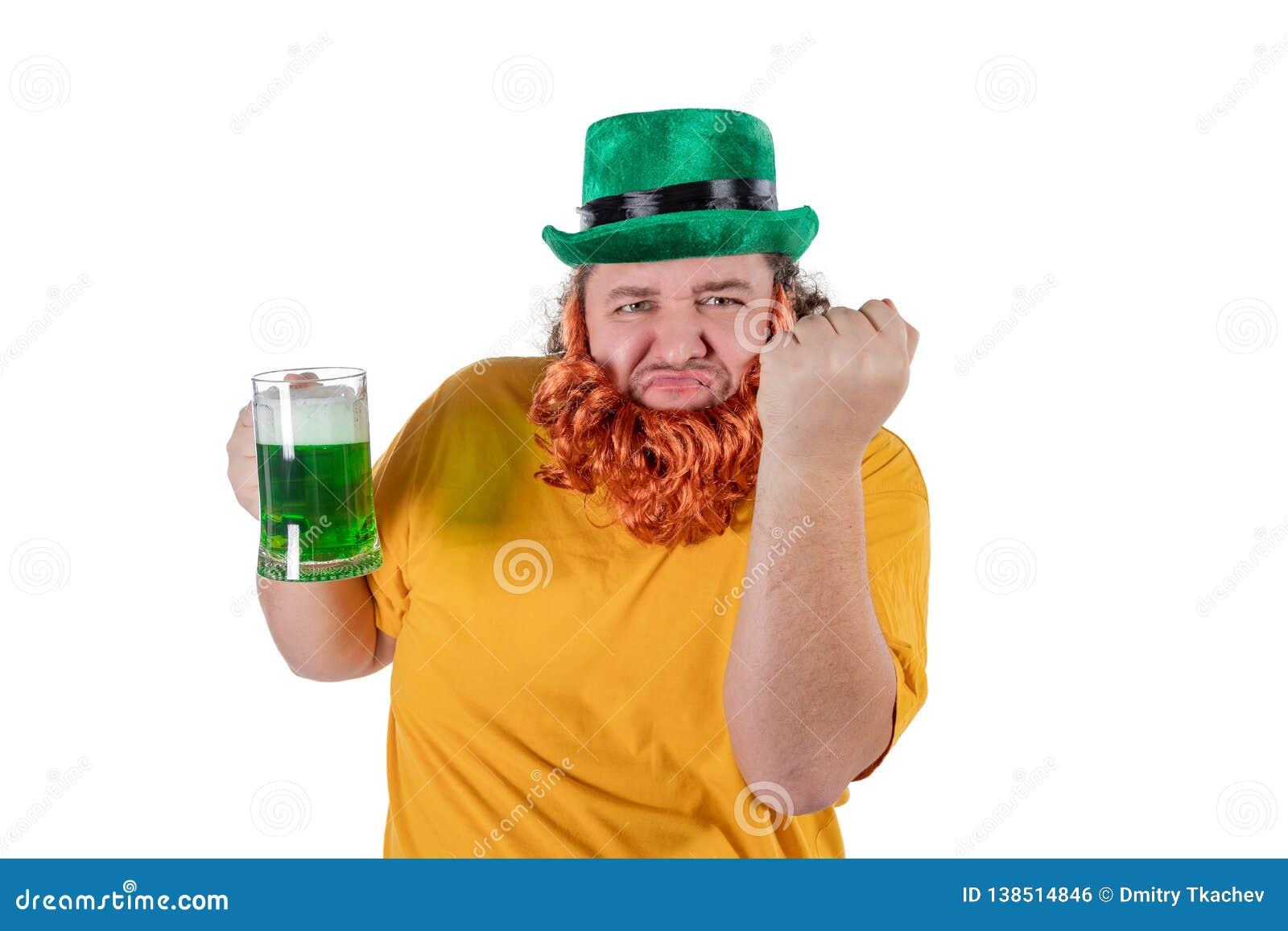 Een glimlachende gelukkige vette mens in een kabouterhoed met groen bier bij studio Hij viert St Patrick