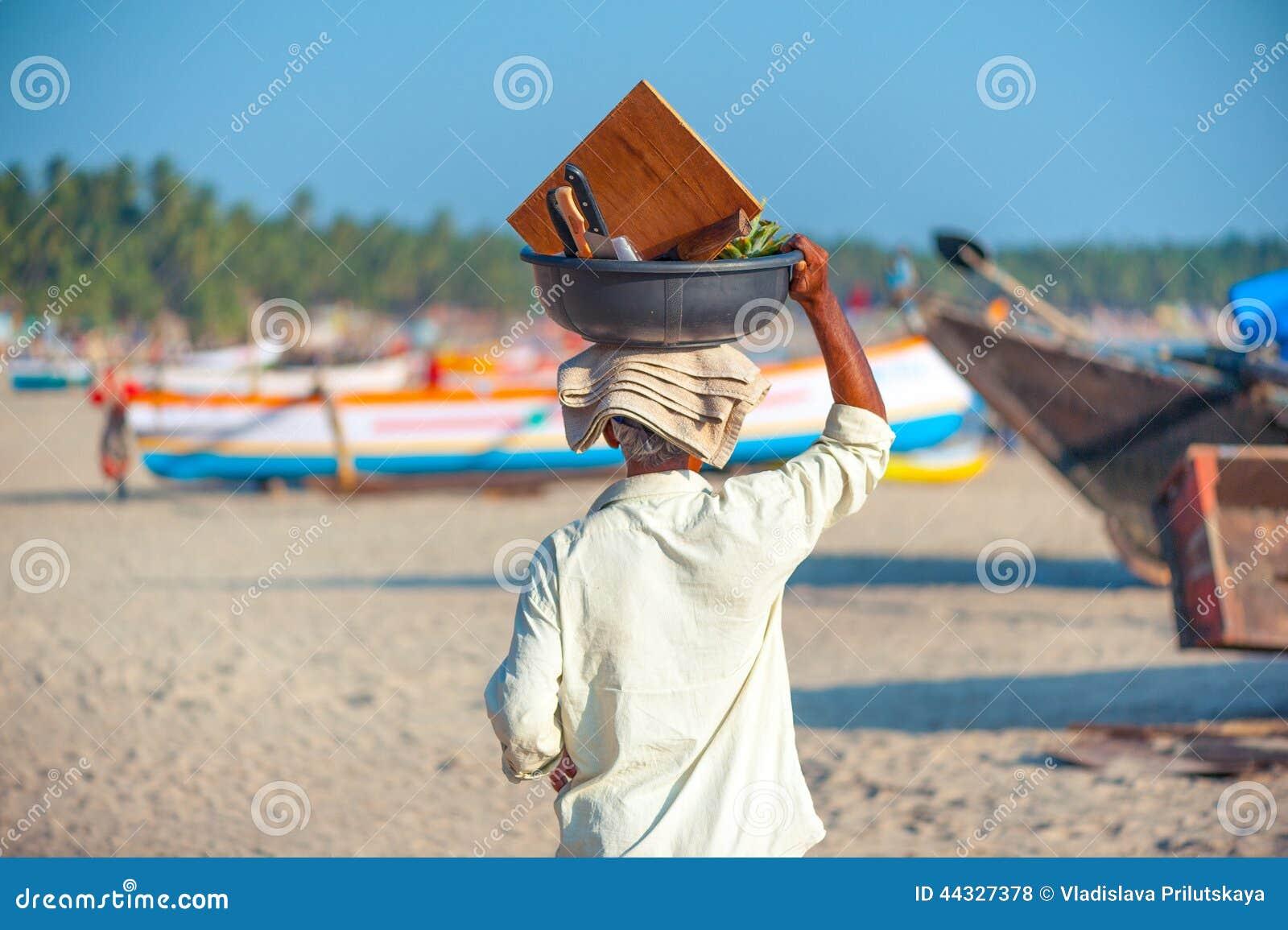 Een goan mens het dragen mandhoogtepunt van vruchten op de bovenkant van zijn hoofd