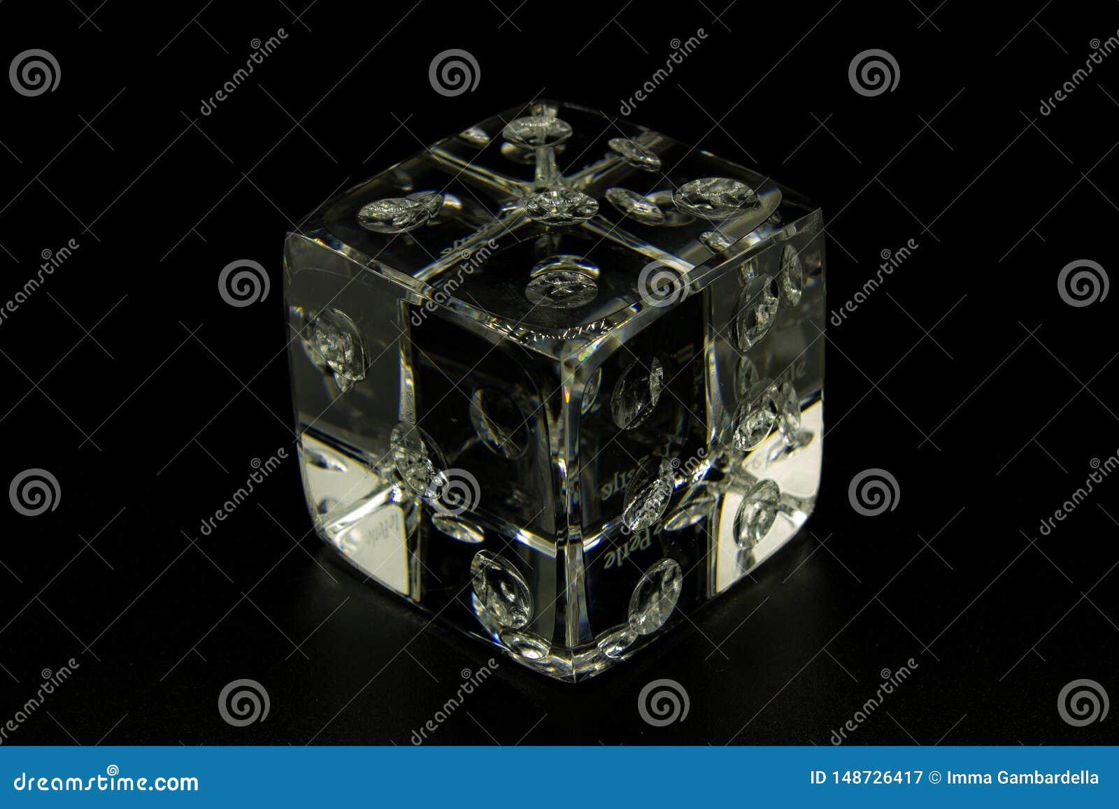 Een gokken dobbelt gemaakt van glas op een zwarte achtergrond, om transparantie te benadrukken