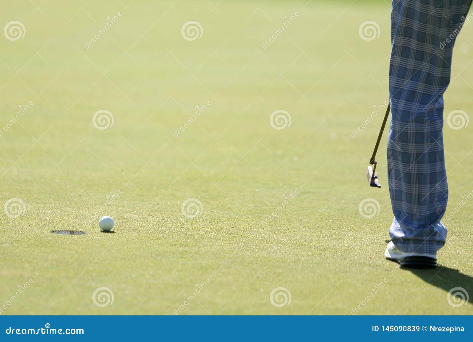 Een golfspeler doet het zetten aan een gat