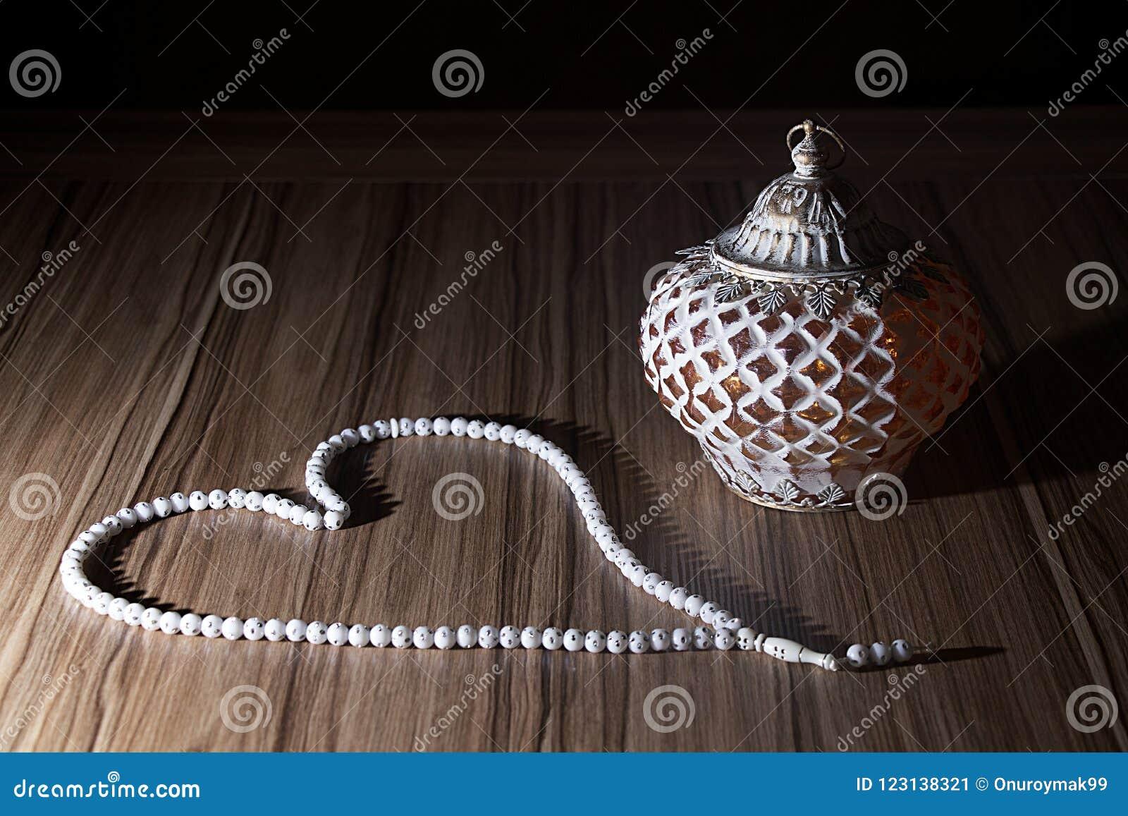 Een gouden lichte Ramadhan-kaars met Islamitische witte rozentuin parelt o