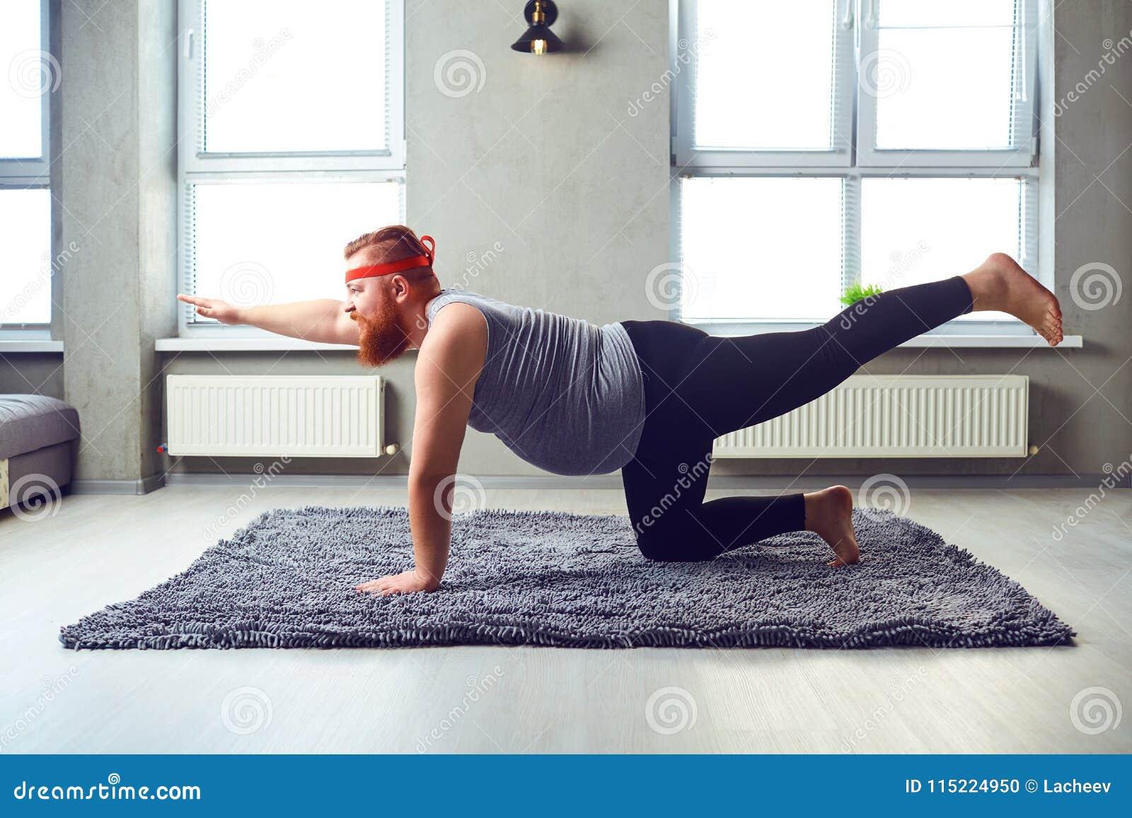 Een grappige vette gebaarde mens in sportenkleren doet yoga in de ruimte