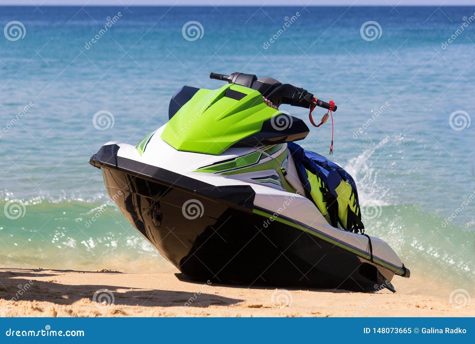 Een groen-witte straalski is op een strand in golven van blauwe overzees in het zonnige weer De actieve rust is gelukkige tijd vo