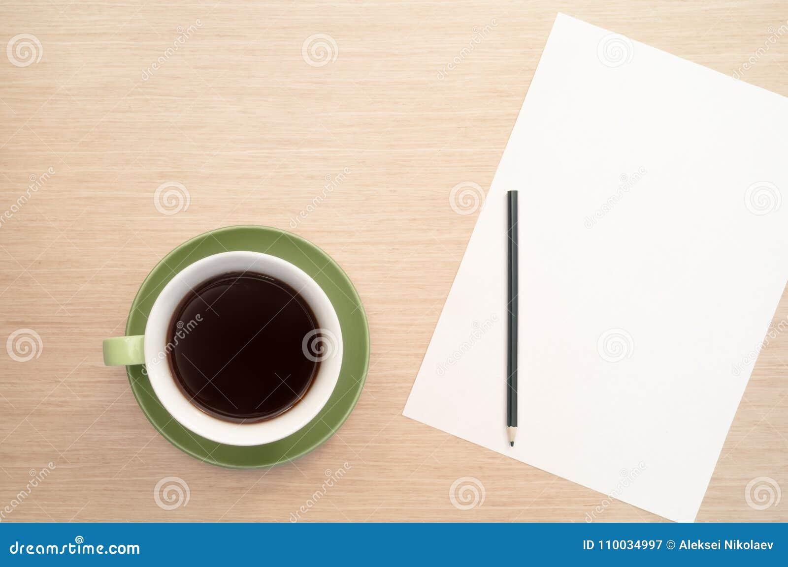Een groene kop van koffie op de achtergrond van een lijst en een wit shee en een potlood