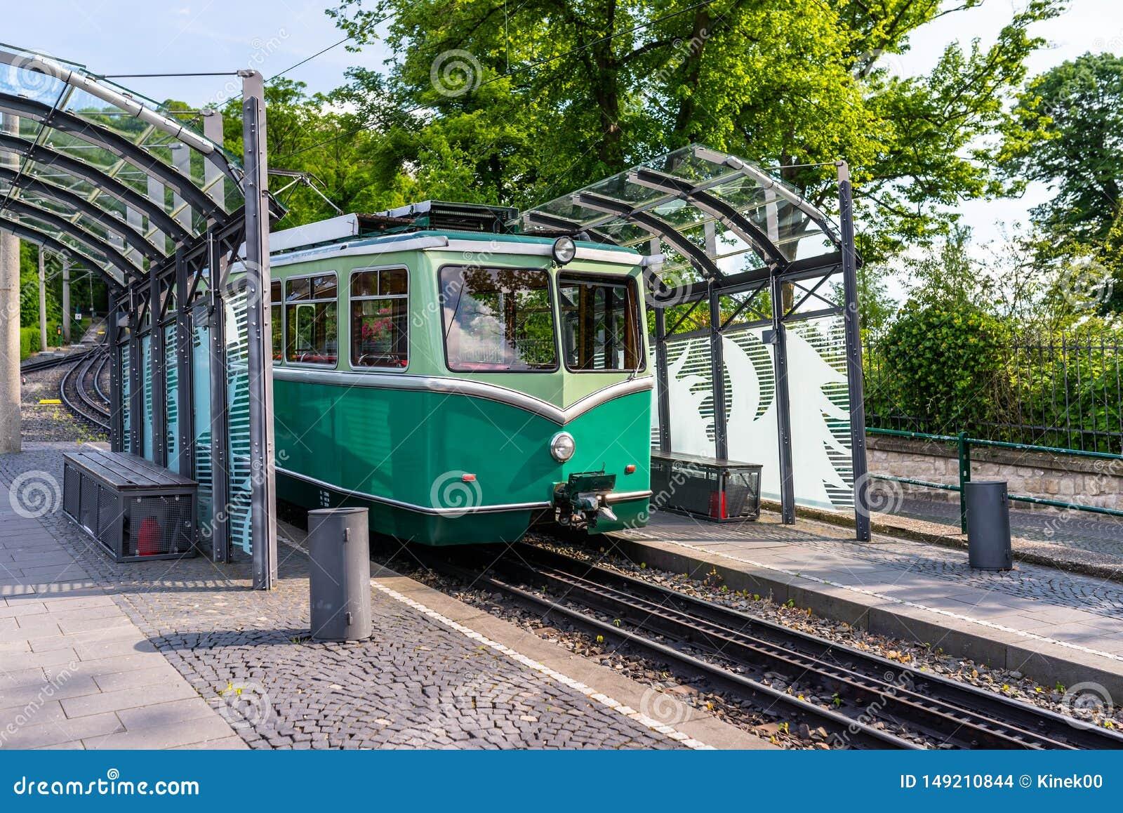 Een groene tandradbaanauto die zich op de sporen bij de bushalte bevinden