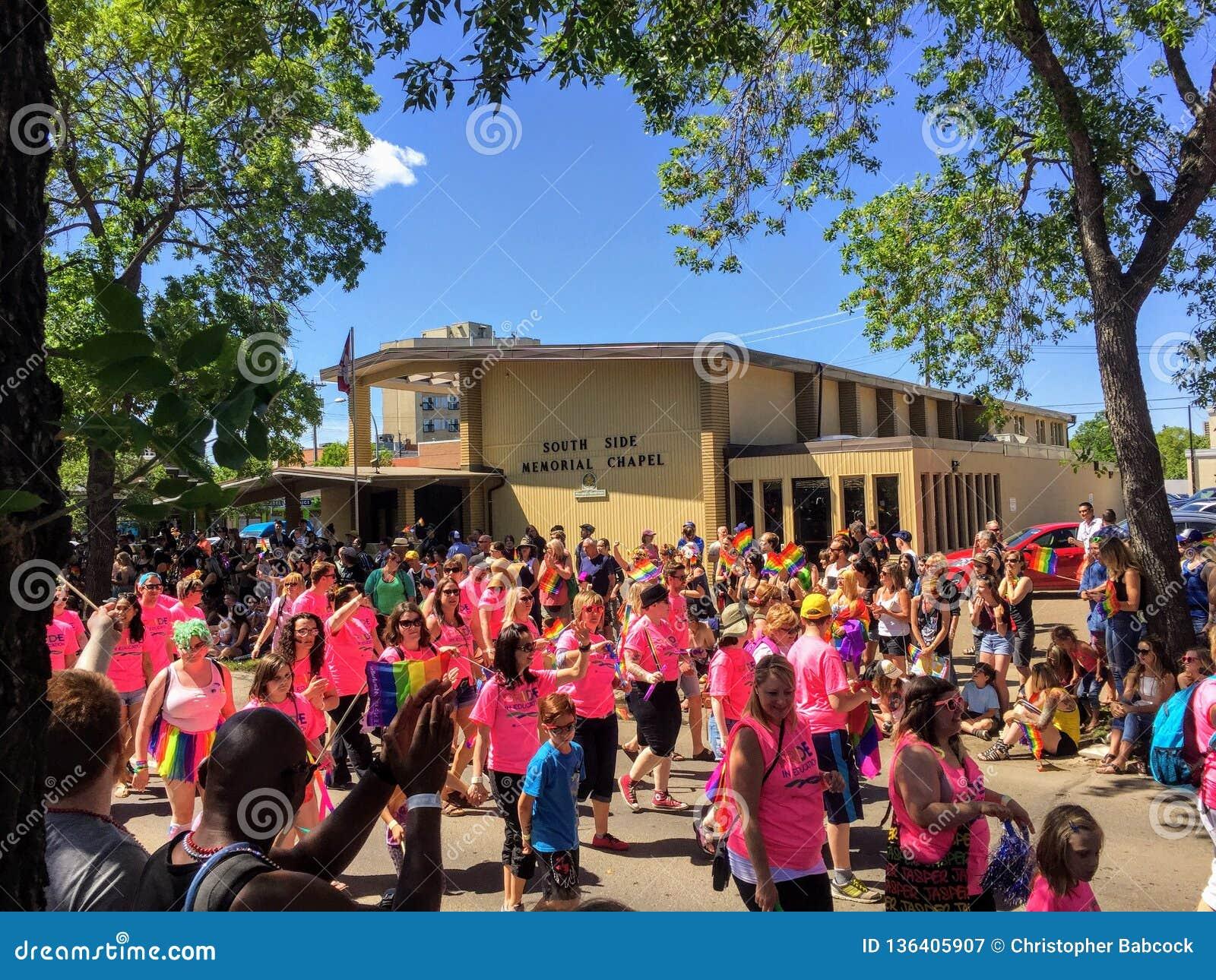 Een groep die mensen in de vrolijke trotsparade dichtbij Whyte-Weg, in Edmonton, Alberta, Canada lopen Veel onze jonge families p