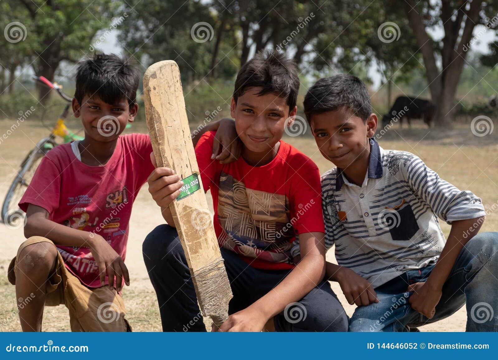 Een groep jongens stelt voor een foto terwijl het spelen van veenmol buiten Bhadarsa